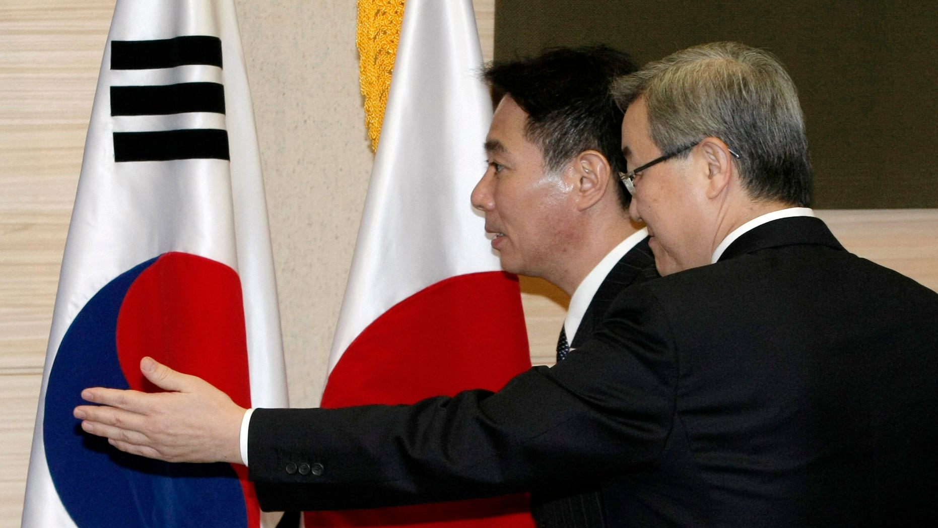 Japanese Foreign Minister Seiji Maehara, back, is escorted by South Korean counterpart Kim Sung-hwan as they arrive to hold their joint press conference at the Ministry of Foreign Affairs and Trade in Seoul, South Korea, Saturday, Jan. 15, 2011. The top diplomats of South Korea and Japan are continuing their hard line on North Korea's push for aid-for-nuclear disarmament talks.