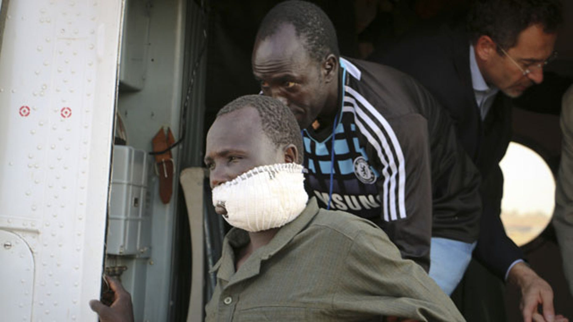 December 22, 2013: In this photo released by the United Nations Mission in South Sudan (UNMISS), wounded civilians from Bor, the capital of Jonglei state and said to be the scene of fierce clashes between government troops and rebels, are assisted after being transported by U.N. helicopter to Juba, South Sudan (AP/UNMISS)