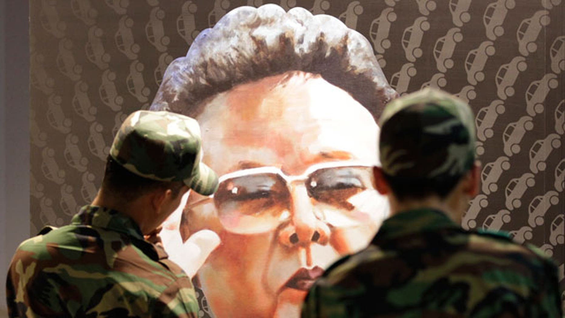 South Korean soldiers look at a poster of North Korean leader Kim Jong Il, painted by North Korean defector Sun Moo, at the Korean War exhibition in Seoul, South Korea, Wednesday, July 7, 2010. North Korea sent nearly three dozen relatives of former economic officials to a prison camp over the country's botched currency reform, a South Korean aid group Good Friends said on its website Tuesday.