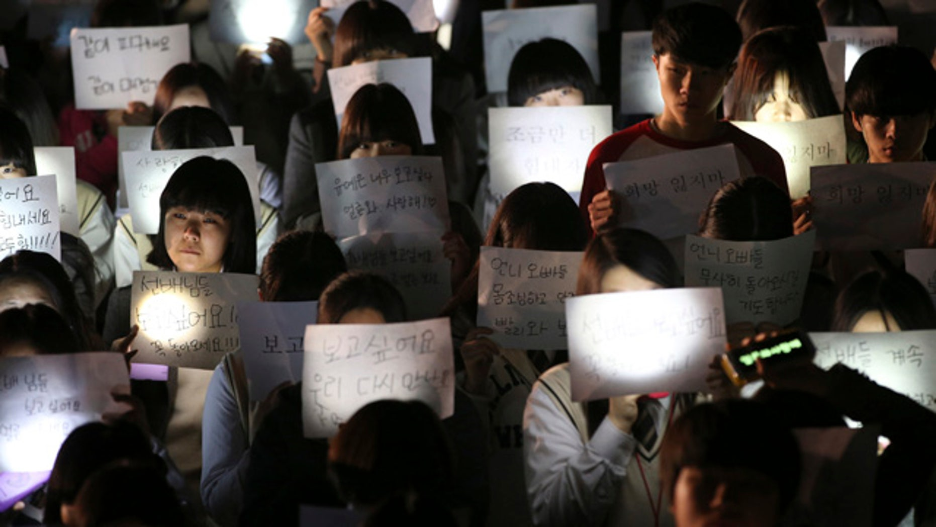 April 18, 2014: Students hold papers with candles as they pray for the safe return of their friends aboard the sunken ferry Sewol at Danwon High School in Ansan, south of Seoul, South Korea. (AP Photo/Yonhap)