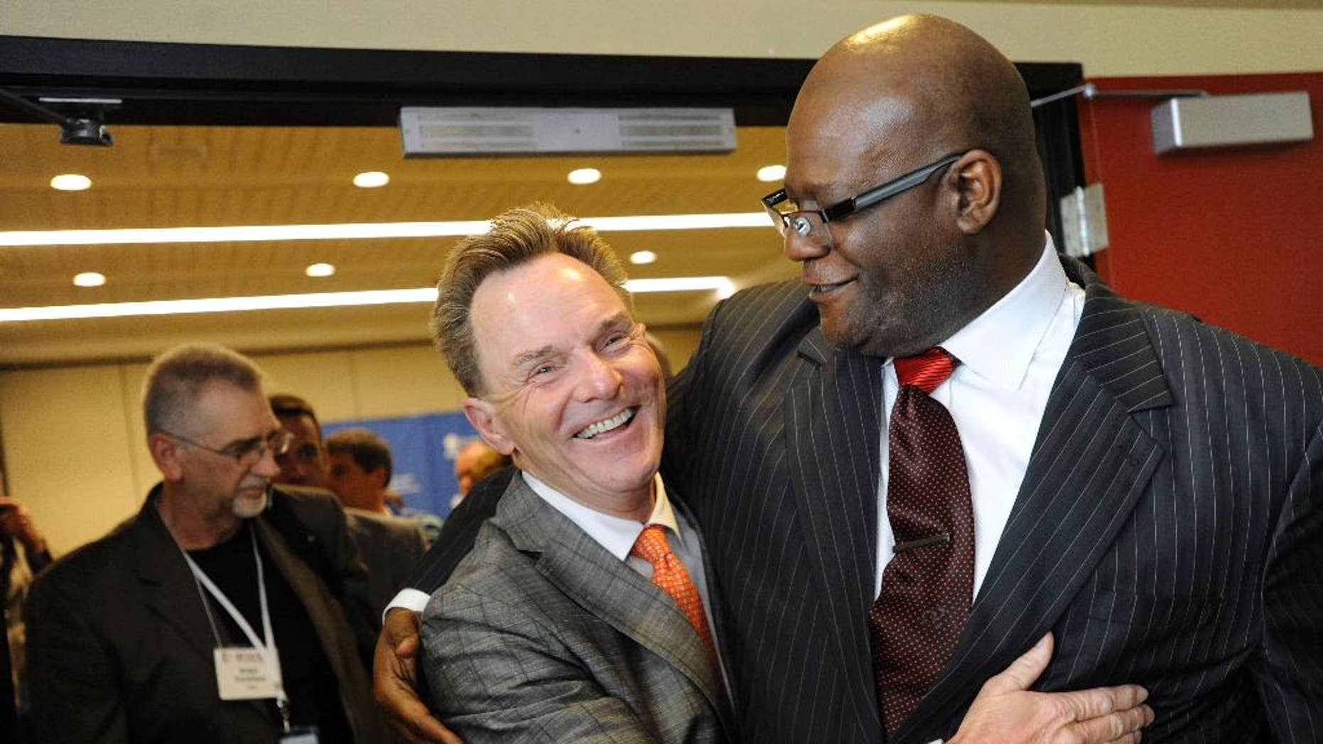 The Rev. Ronnie Floyd, center, of Cross Church in northwest Arkansas, hugs The Rev. Dwight McKissic, right, of Cornerstone Baptist Church in Arlington, Texas, after Floyd was elected the new president of the Southern Baptist Convention during its annual meeting Tuesday, June 10, 2014, in Baltimore. Floyd received 52 percent of votes cast by delegates to the annual meeting of the nation's largest Protestant denomination. (AP Photo/Steve Ruark)