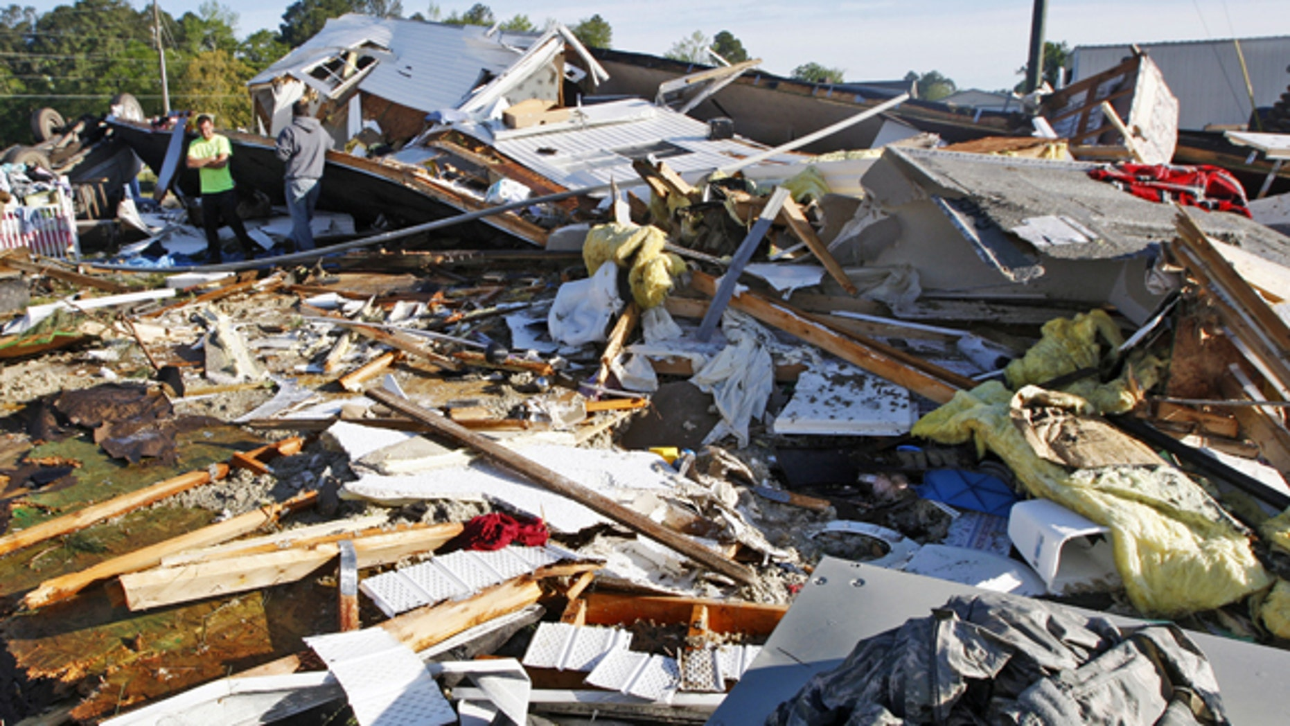 April 26, 2014: People stand among the remains of a mobile home that was destroyed when a tornado touched down along Black Jack-Simpson Road  in Greenville, N.C. the previous day.  (AP Photo/The Daily Reflector, Aileen Devlin)