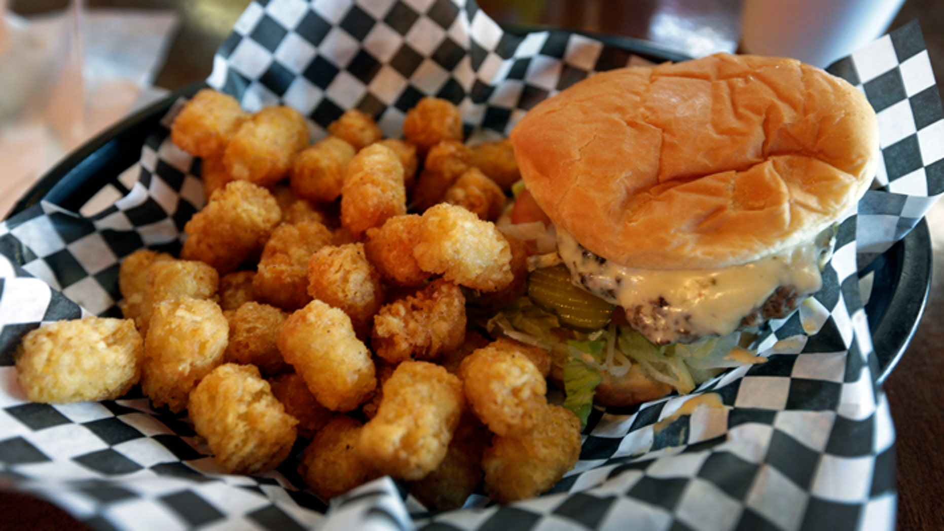 This Wednesday, Feb. 6, 2013 photo shows a hamburger and tater tots at a restaurant in Charlotte, N.C. Deep-fried foods may be causing trouble in the Deep South. People whose diets are heavy on them and sugary drinks were more likely to suffer a stroke, according to a new study released Thursday, Feb. 7, 2013. (AP Photo/Chuck Burton)