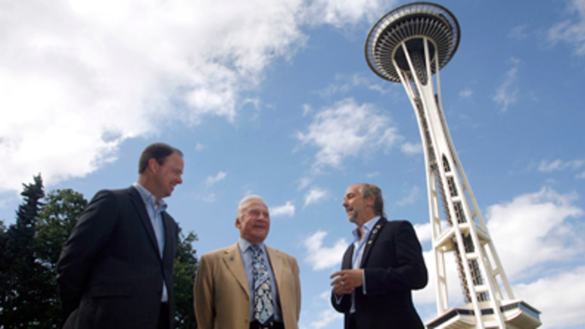 Buzz Aldrin, former astronaut, center, and Richard Garriott, first second-generation space traveler, right, talk about space exploration outside the Space Needle on Sunday, July 31, 2011, in Seattle as Ron Sevart, CEO of the Space Needle, left, listens in. Aldrin and Garriott were at the Space Needle to help promote a contest sponsored by the Needle to celebrate its 50th anniversary by sending a member of the general public into space.     (AP Photo/Joe Nicholson)
