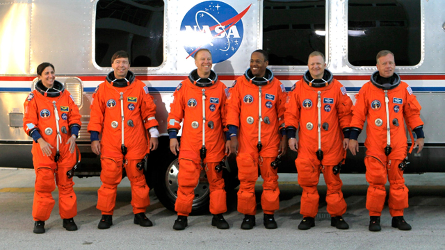 The crew of space shuttle Discovery, from left, mission specialists Nicole Stott, Michael Barratt, Tim Kopra and Alvin Drew, pilot Eric Boe and commander Steve Lindsey, leave the Operations and Checkout Building to board the shuttle at pad 39A for a launch dress rehearsal at the Kennedy Space Center in Cape Canaveral, Fla., Friday, Oct. 15, 2010. Discovery is scheduled to launch Nov. 1.