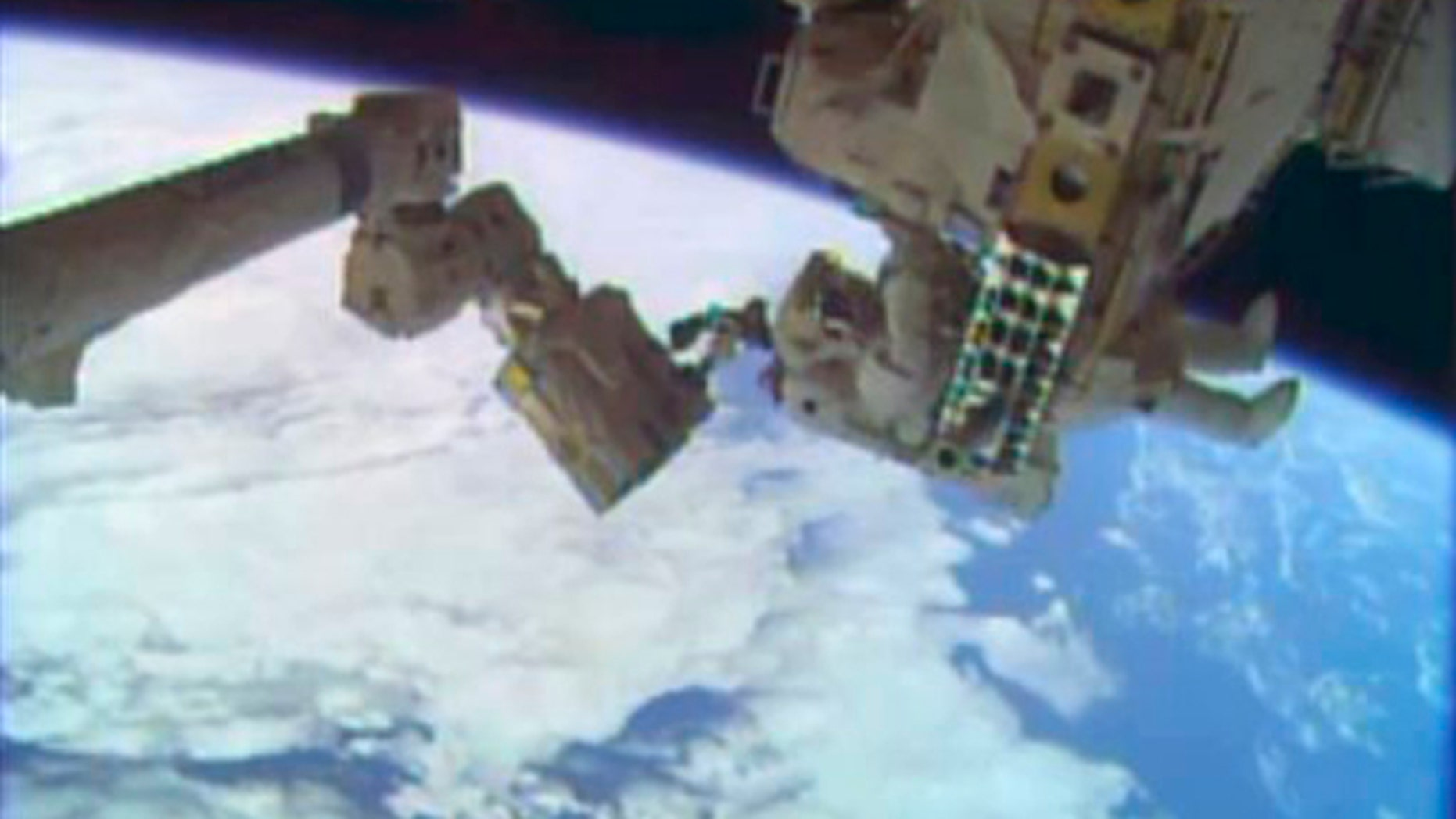 In this image taken from video provided by NASA, astronauts Rick Mastracchio, top, and Michael Hopkins work to repair an external cooling line on the International Space Station on Monday, Dec. 24, 2013, 260 miles above Earth. The external cooling line â one of two â shut down Dec. 11. The six-man crew had to turn off all nonessential equipment, including experiments. (AP Photo/NASA)