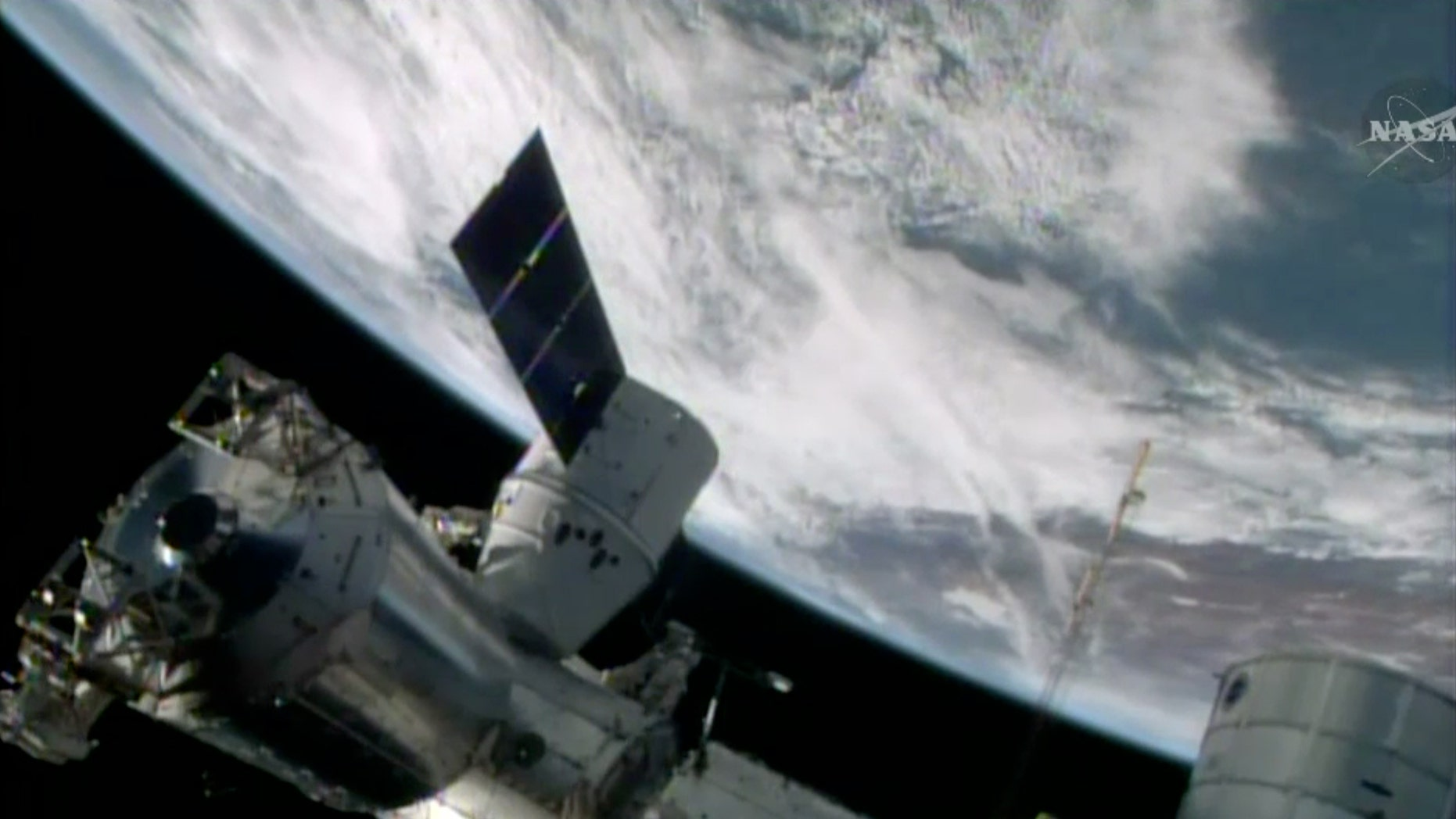 FILE- In this April 20, 2014, image made from a frame grabbed from NASA-TV, the SpaceX Dragon resupply capsule begins the process of being berthed on to the ISS.
