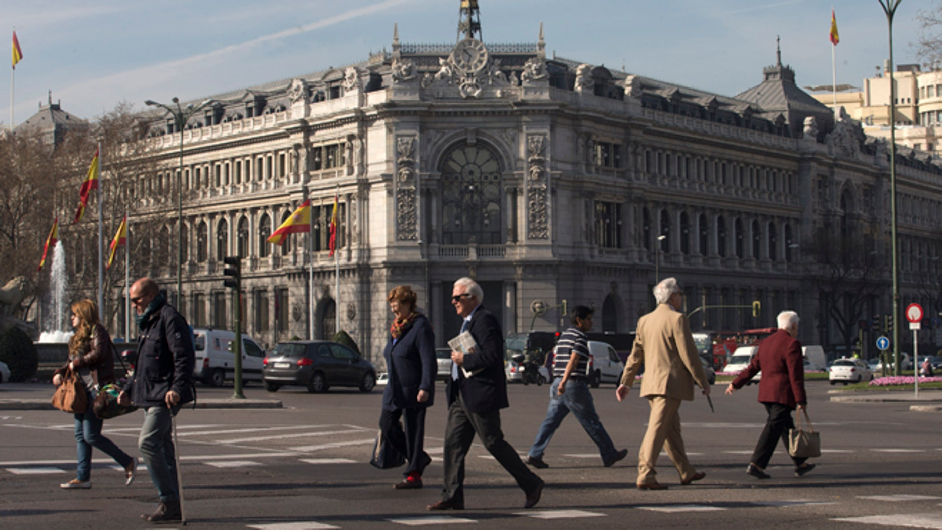 People cross the street in front of Spain's Central Bank in Madrid, Spain, Thursday, March 12, 2015. The entire board of Spainâs Banco de Madrid bank catering to wealthy clients has resigned after its Andorran owner was accused by the U.S. of money laundering for clients from China, Russia and Venezuela, Banco de Madrid said Thursday. (AP Photo/Paul White)
