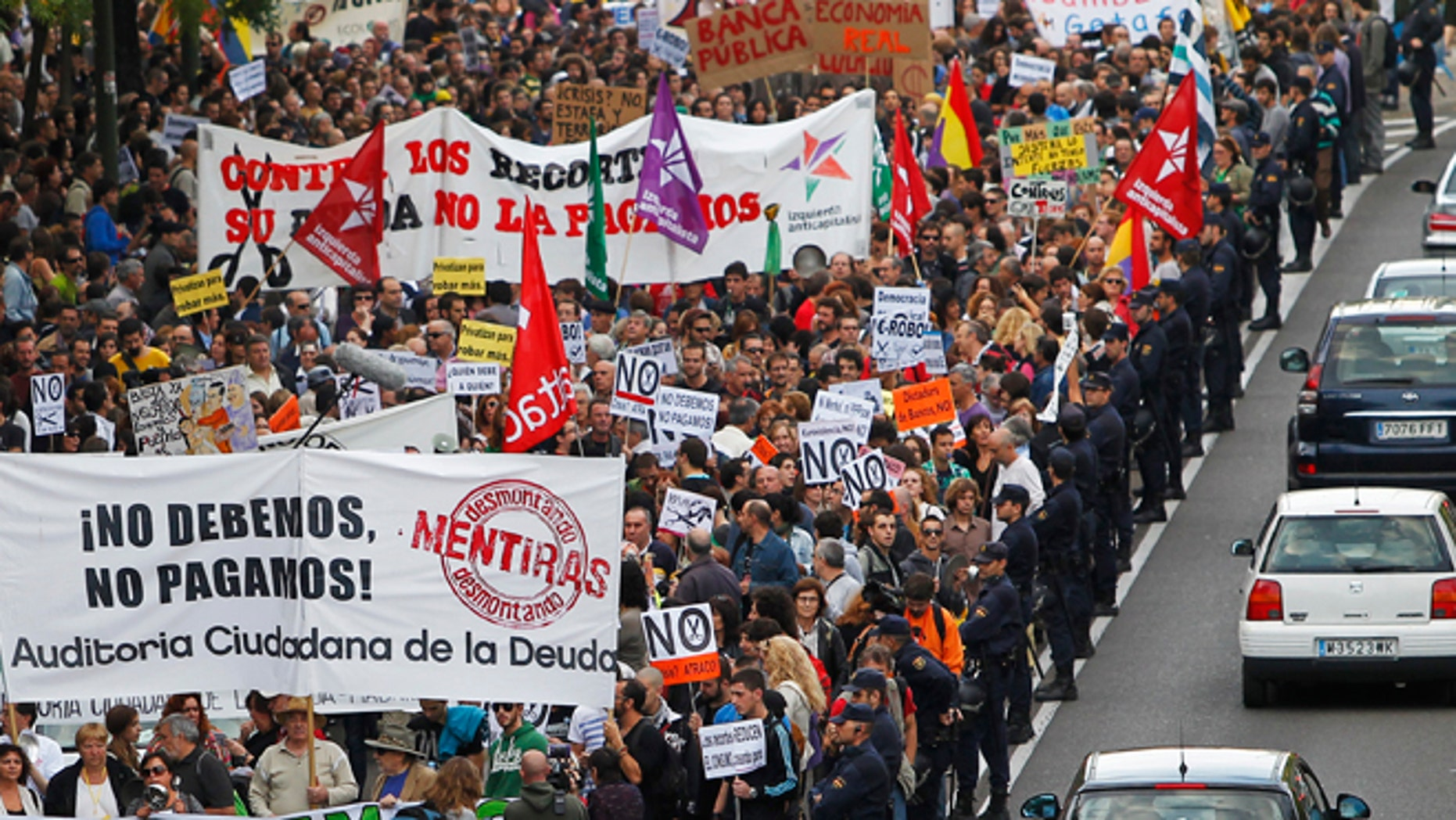 Protestor march as they hold banners reading âWe don't owe, we won't payâ against austerity measures announced by the Spanish government in Madrid, Spain, Saturday, Oct. 13, 2012. Several thousand people noisily banging pots and pans marched down Madrid's main north-to-south boulevard protesting the government's austerity measures. With unemployment nearing 25 percent, Spain has introduced biting austerity measure as well as financial and labor reforms in a desperate bid to lower its deficit and assuage investors' misgivings. (AP Photo/Andres Kudacki)