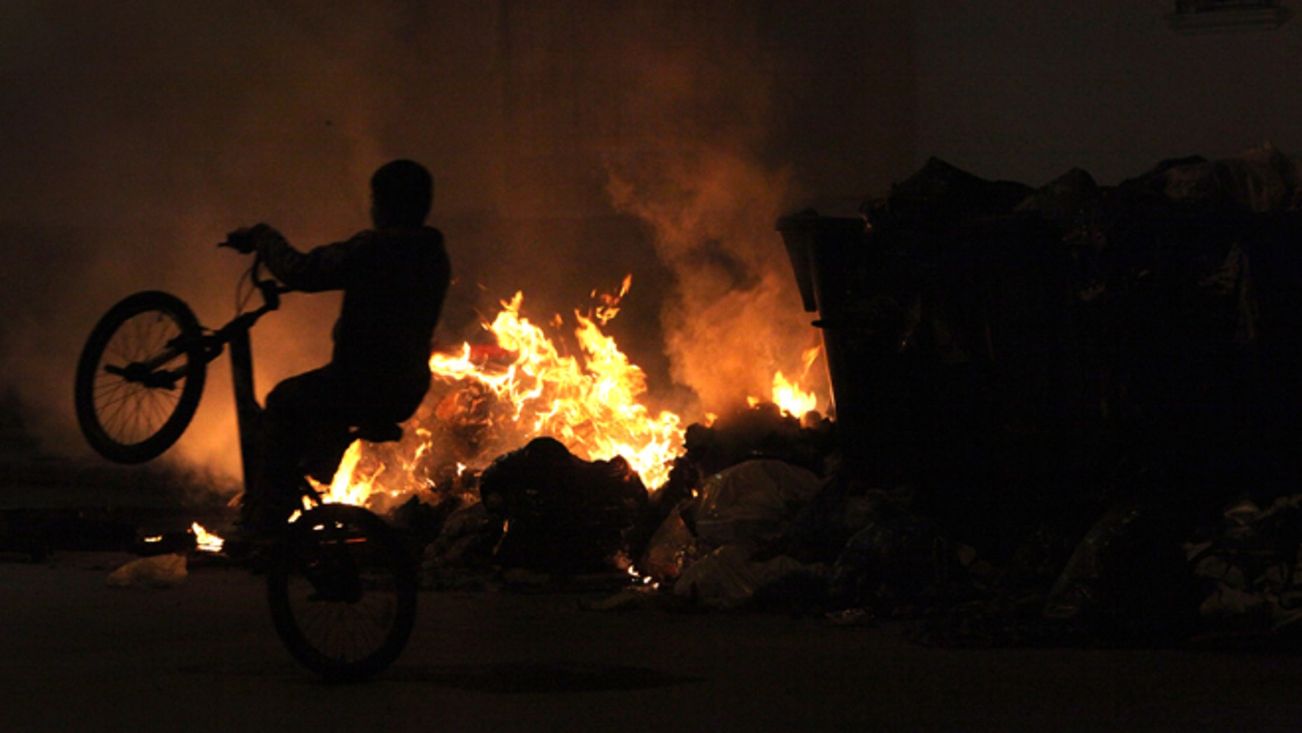 A boy rides his bicycle next to burning garbage piled up in the middle of the street in Jerez de la Frontera, Cadiz province in Andalucia, southern Spain Wednesday, Nov. 21, 2012. A garbage strike has been ongoing now for nineteen days and has resulted in more than 3,000 tons of garbage piled up on the streets and the burning of rubbish containers by local residents.  (AP Photo/Javier Fergo)