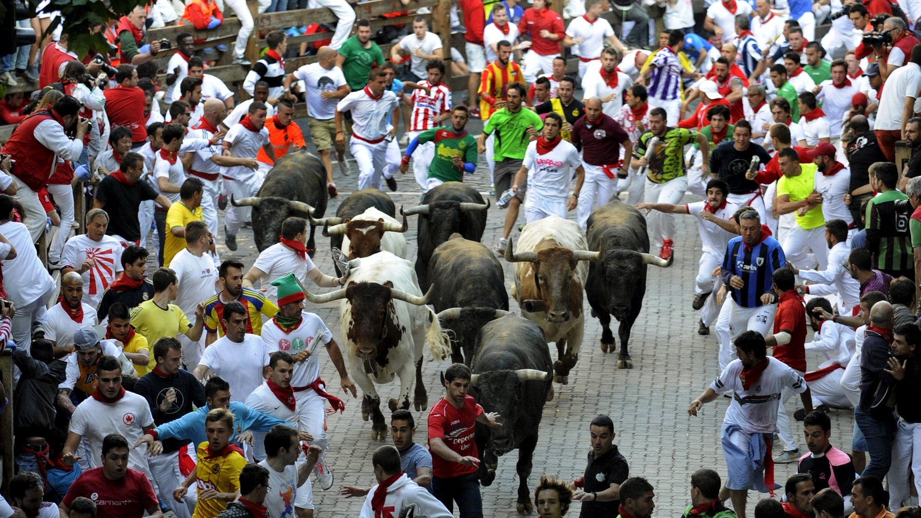 July 14, 2015 - FILE photo of runners sprinting alongside Miura fighting bulls at the entrance to the bullring on the last day of the running of the bulls of the San Fermin festival in Pamplona, northern Spain. A Spanish mayor says a man has died after being gored while videoing a bull-run with his cell phone.