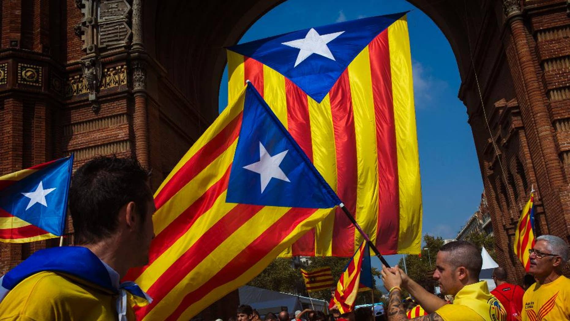 """People wave """"estelada"""" flags, that symbolize Catalonia's independence, in Barcelona, Spain, Thursday, Sept 11, 2014. A week before Scotland votes on whether to break away from the United Kingdom, separatists in northeastern Spain were trying to convince hundreds of thousands to protest across Catalonia to demand a secession sentiment vote that the central government in Madrid insists would be illegal. (AP Photo/Emilio Morenatti)"""