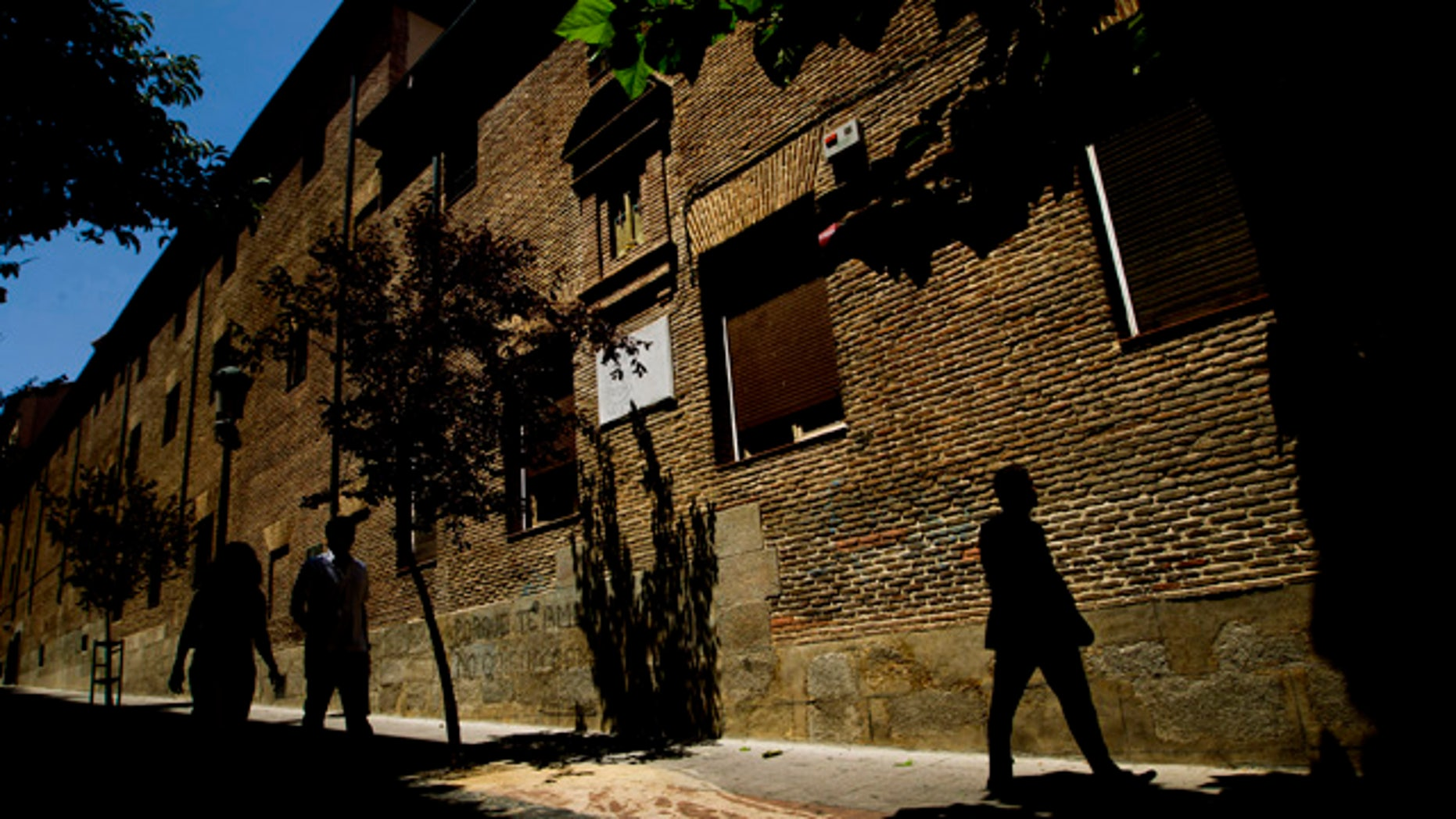 FILE - In this July 28, 2011 file photo, pedestrians walk by the closed order convent of the Trinitarias Descalzas, where the Spanish writer Miguel de Cervantes, author of  El Quijojte, was buried in Madrid, Spain. His coffin and remains were lost during construction work at the church. (AP Photo/Daniel Ochoa de Olza, File)