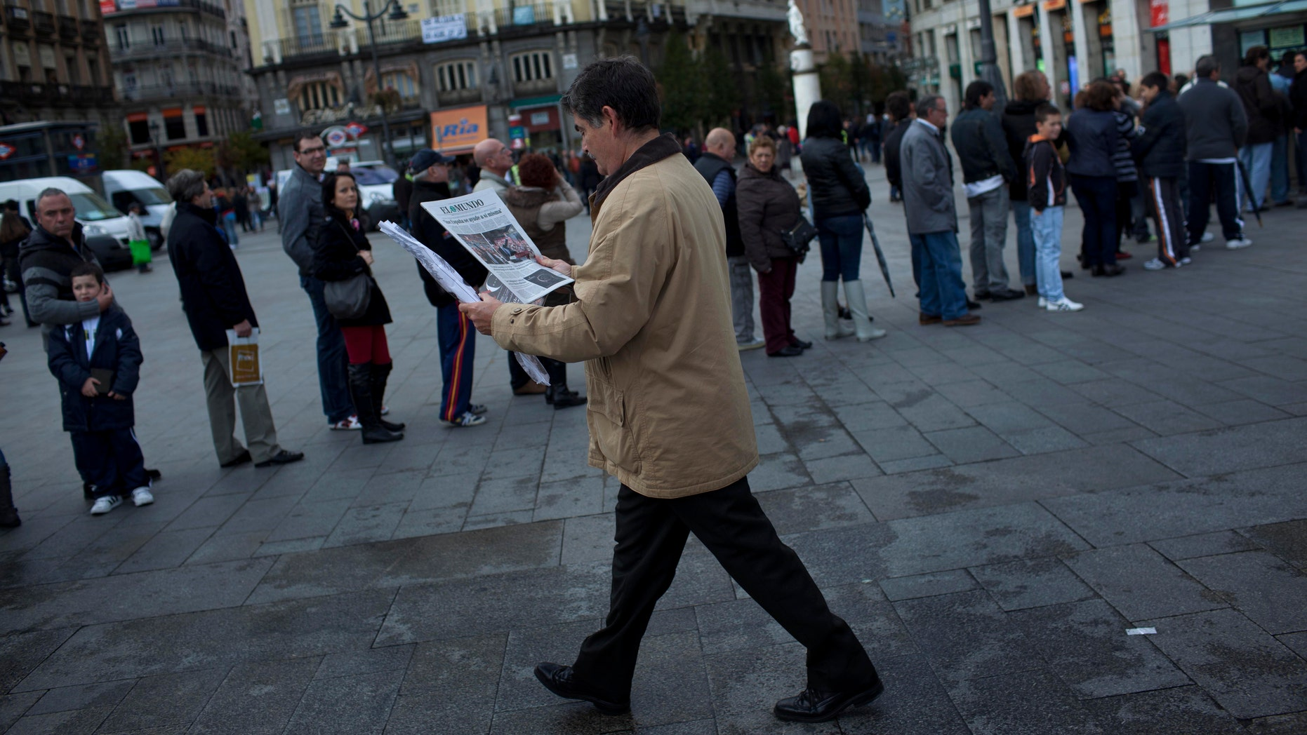 A man reads the news about the Spanish electoral campaign as others line up waiting to buy lottery in Madrid, Spain, Saturday, Nov. 19, 2011.  Spain will hold general elections on Nov. 20. (AP Photo/Emilio Morenatti)