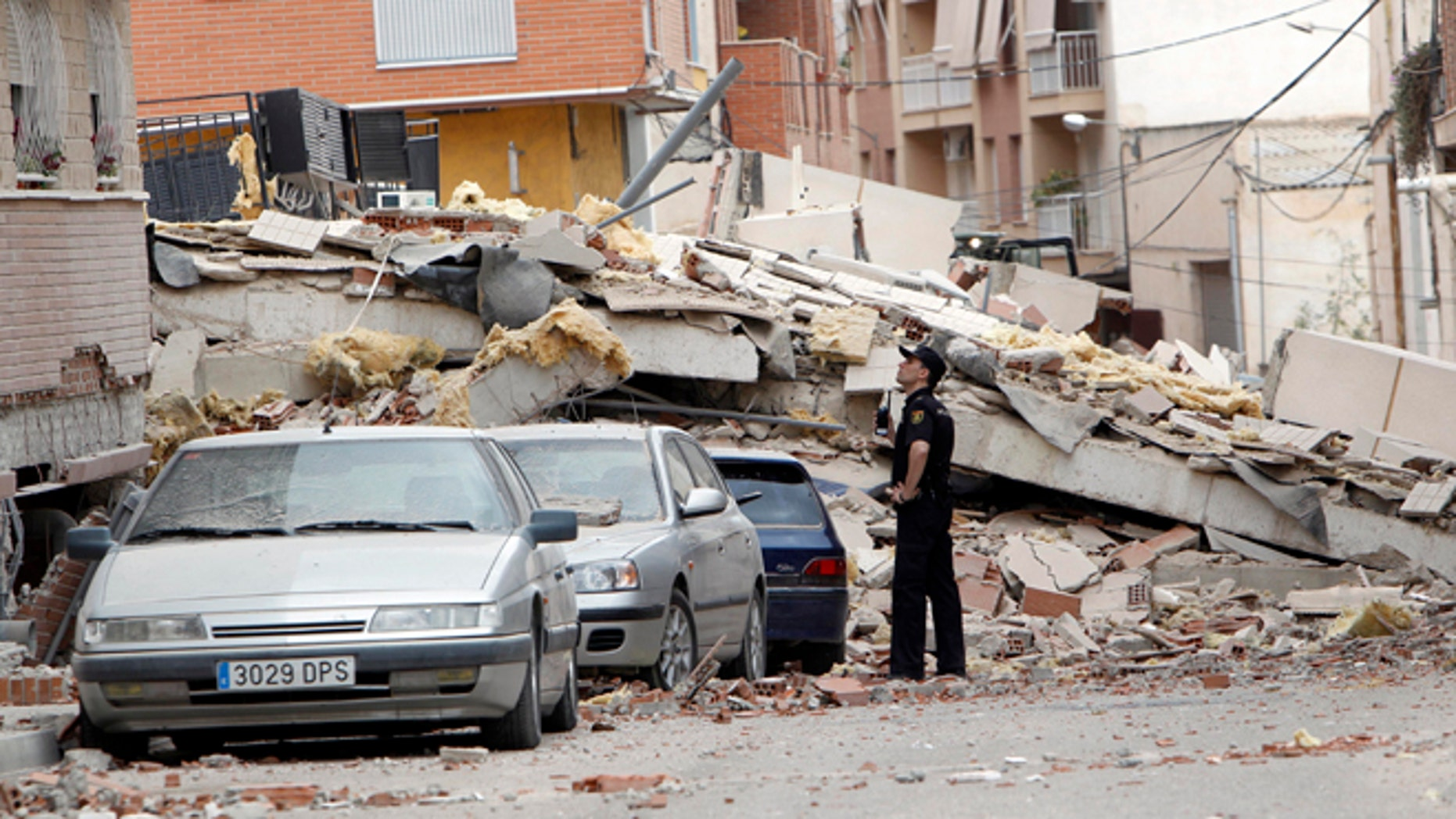 May 12, 2011: A police officer inspects damage caused by an earthquake the previous day in Lorca, Spain. Farmers drilling ever deeper wells over decades to water their crops likely contributed to the deadly earthquake in southern Spain last year, a new study suggests.