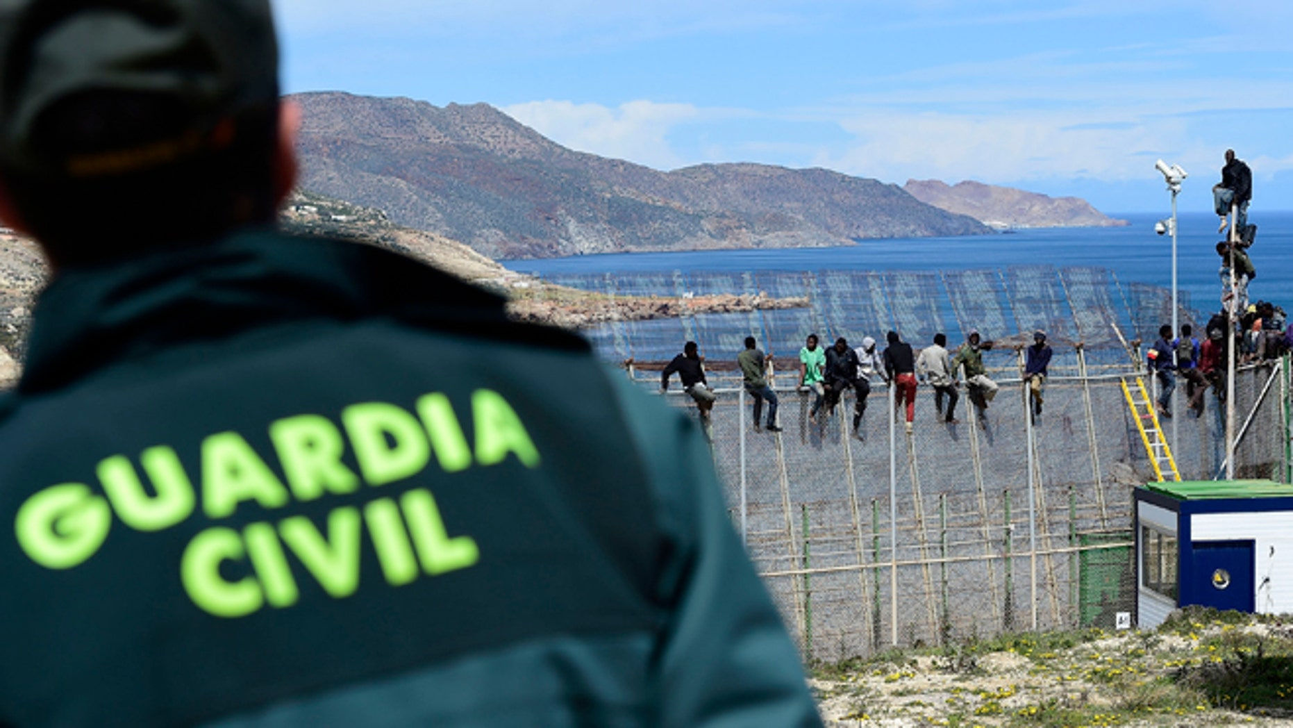 MELILLA, SPAIN - APRIL 03:  A Guardia Civil Police Officer watches African migrants who attemped to scale the fence at the border between Morocco and the North African Spanish enclave of Melilla, on April 3, 2014, in Melilla, Spain. Roughly 70 sub-Saharan migrants tried climb the fence into Melilla this morning, one had to be treated by paramedics. Melilla is a Spanish city and an exclave on the north coast of Africa sharing a border with Morocco. Almost one week ago Some 800 sub- Saharan people made several attempts to reach Spain and according to official sources, ten of them managed to enter Spanish territory.  (Photo by Alexander Koerner/Getty Images)