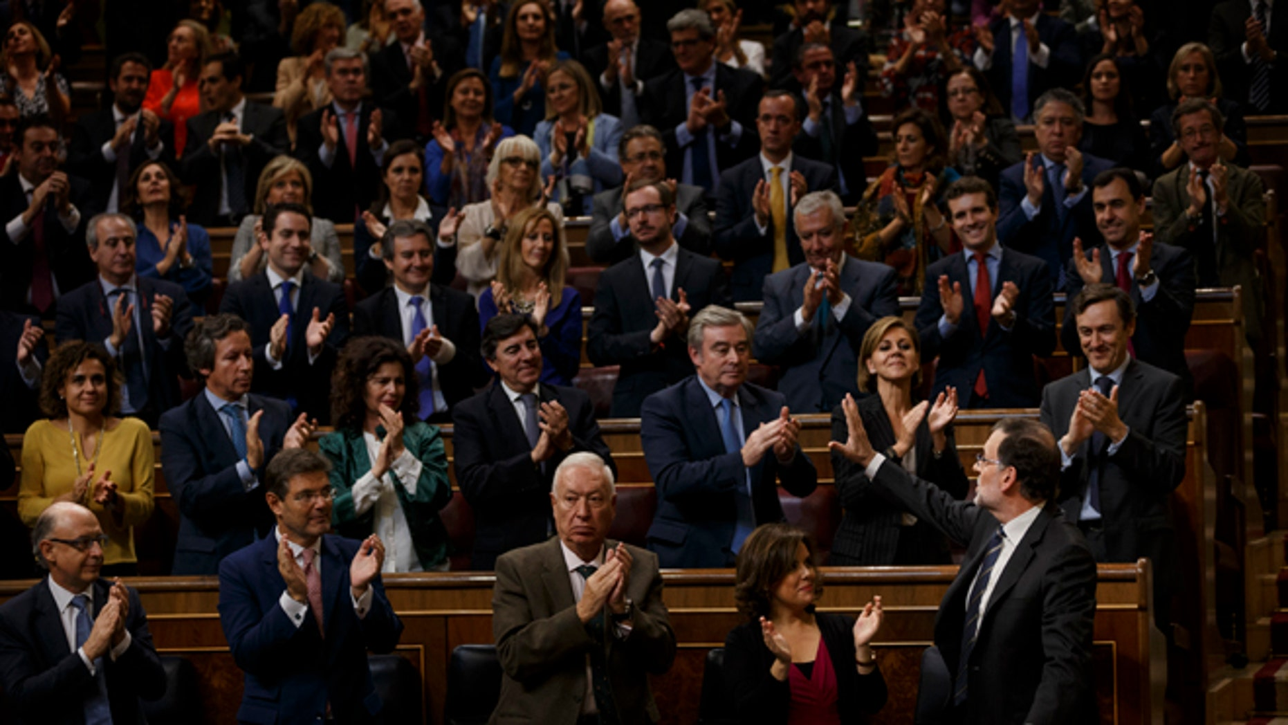 Spain acting conservative Prime Minister and Popular Party leader Mariano Rajoy, right, is greeted by his party members after speaking at the investiture debate, a day before a first confidence vote in Madrid, Spain, Wednesday, Oct. 26, 2016.  The Spanish Parliament has started an investiture debate that is widely expected to end in the conservative Popular Party taking power later this week, ending 10 months of political deadlock during which a caretaker government has run the country. (AP Photo/Daniel Ochoa de Olza)