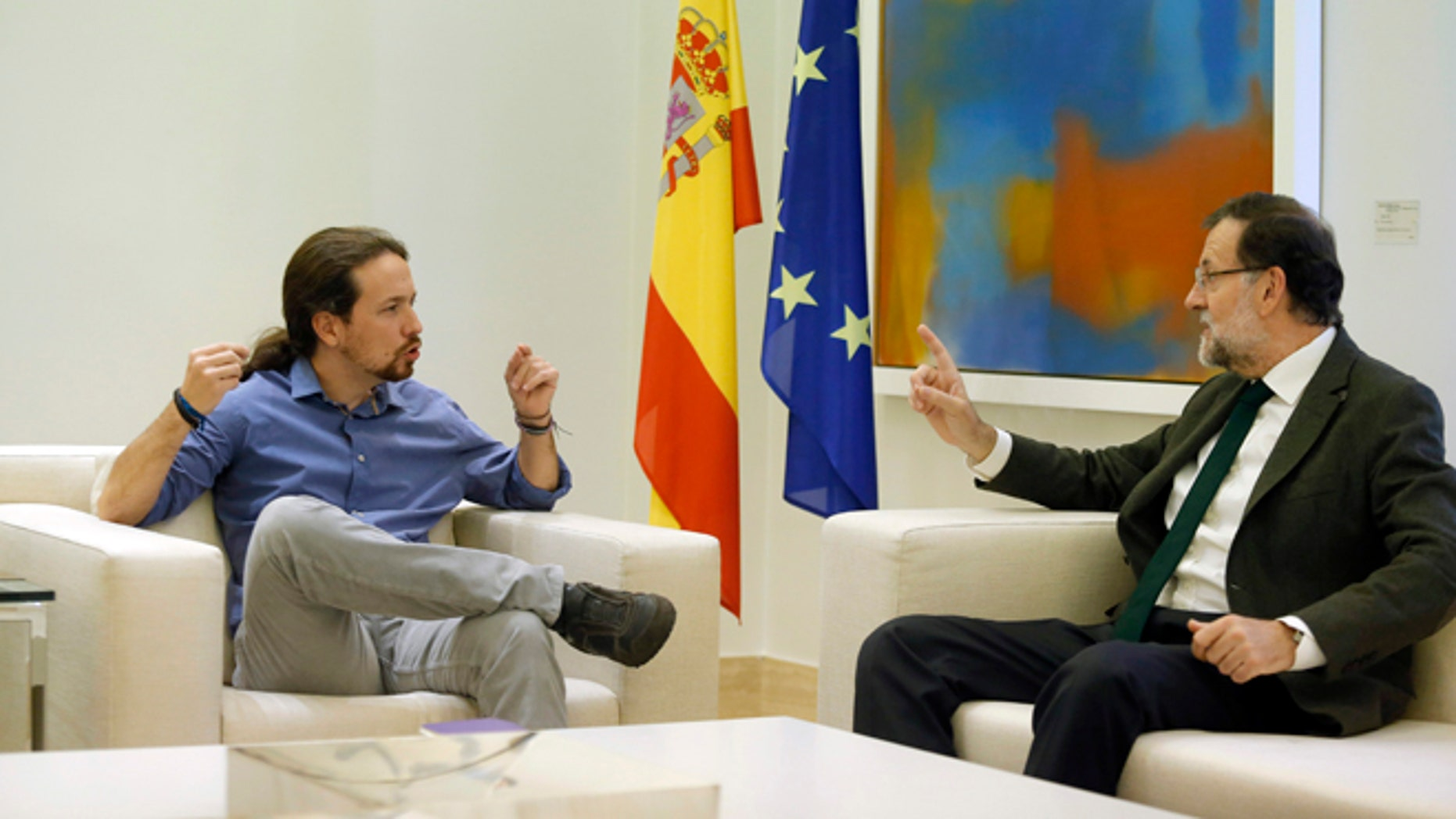 FILE - In this Oct. 30, 2015 file photo, Spain's Prime Minister Mariano Rajoy, right, talks to Podemos party leader Pablo Iglesias during their meeting at the Moncloa palace, the Spanish premier's official residence, in Madrid. Rajoy is meeting with the leaders of two upstart parties on Monday Dec. 28, 2015 following an election that gave Rajoys party the most votes but left it far short of a parliamentary majority. Rajoy is seeking support for his center-right Popular Party to govern as a minority party or in a coalition but his options are limited. (AP Photo/Francisco Seco, File)