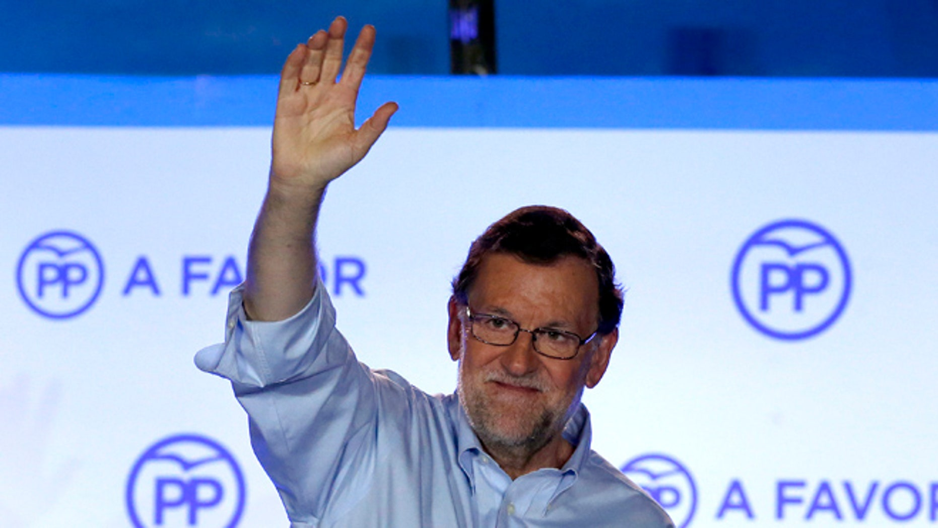 Spain's acting Primer Minister and candidate of Popular Party Mariano Rajoy, waves to his supporters as he celebrates the results of the party during the national elections in Madrid, Spain, Sunday, June 26, 2016. Spain's repeat election on Sunday failed to clarify the political future of the European Union's fifth-largest economy, with the main parties placing roughly the same as in last December's ballot, which brought six months of stalemate. (AP Photo/Daniel Ochoa de Olza)