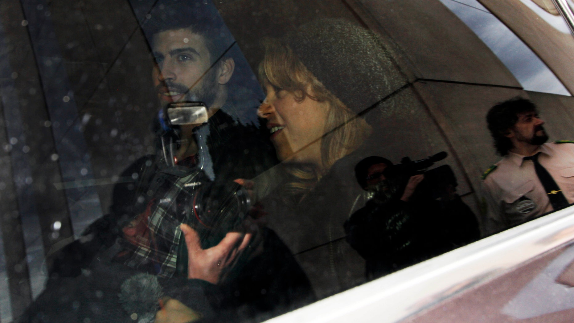 Jan. 27, 2013: FC Barcelona's Gerard Piqué, left, and Shakira, right, and their son, unseen, leave a hospital surrounded by media,  in Barcelona, Spain.