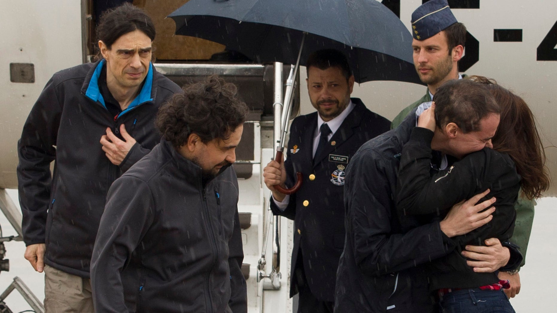 In this photo made available by Presidencia del Gobierno on Sunday, May 8, 2016, the three freed Spanish journalists Antonio Pampliega, right, Jose Manuel Lopez, left, and Angel Sastre, arrive at the Torrejon military airbase in Madrid, Spain. Three Spanish journalists who went missing while working in Syria in July were freed from captivity, the Spanish government said on Saturday. Antonio Pampliega, Jose Manuel Lopez and Angel Sastre disappeared near the city of Aleppo in northern Syria on July 12. (Pool Moncloa via AP)