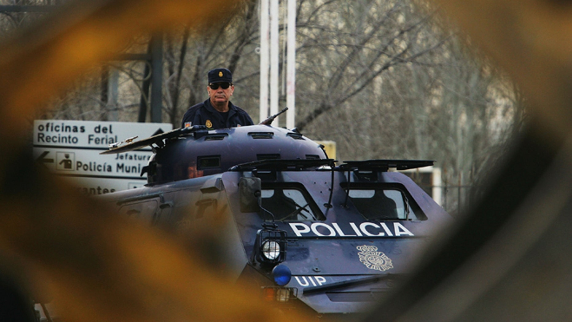 MADRID, SPAIN - FEBRUARY 15:  A digger passes an armoured police vehicle at the Madrid National Court in the Casa de Campo, on the first day of the Madrid train bombings trial, on February 15, 2007 in Madrid, Spain. The March 2004 attack on commuter trains killed 119 and wounded 1,700 people. (Photo by Denis Doyle/Getty Images)