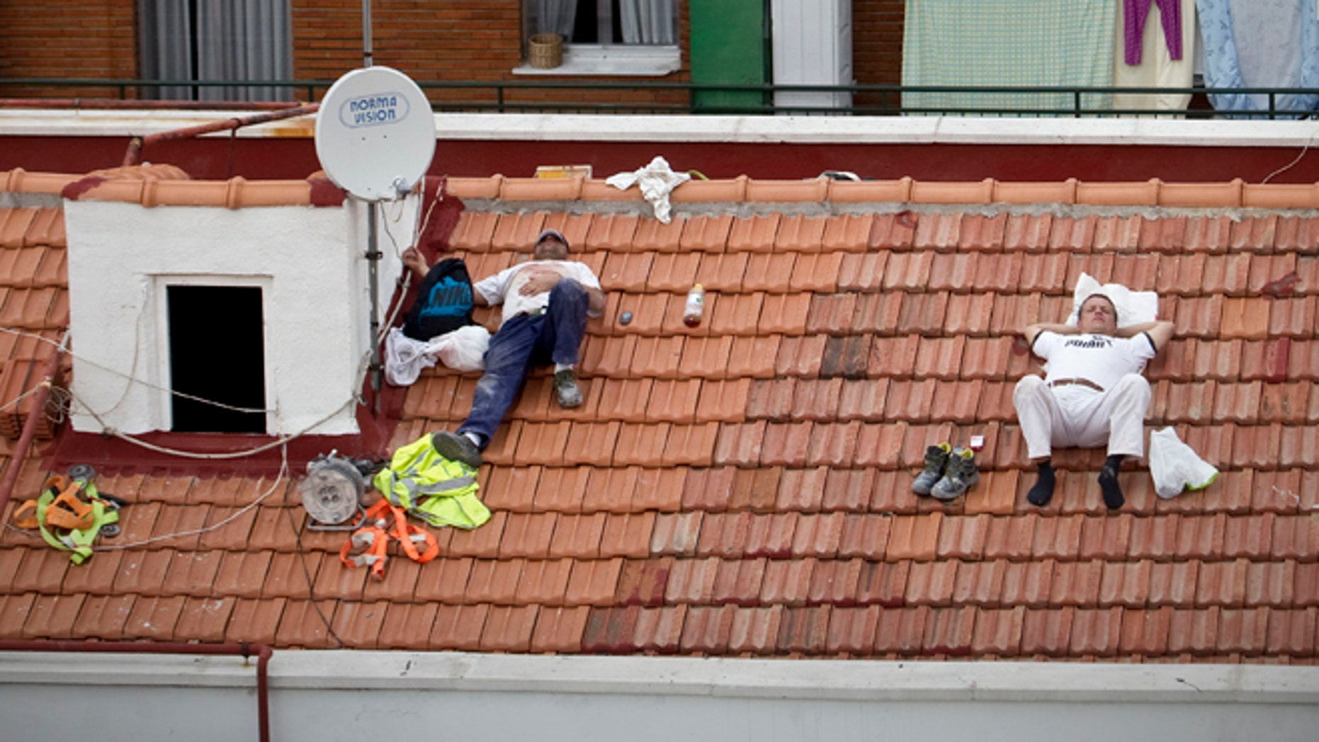In this Oct. 10, 2012 file photo, workers take a nap on a roof in Madrid, Spain.