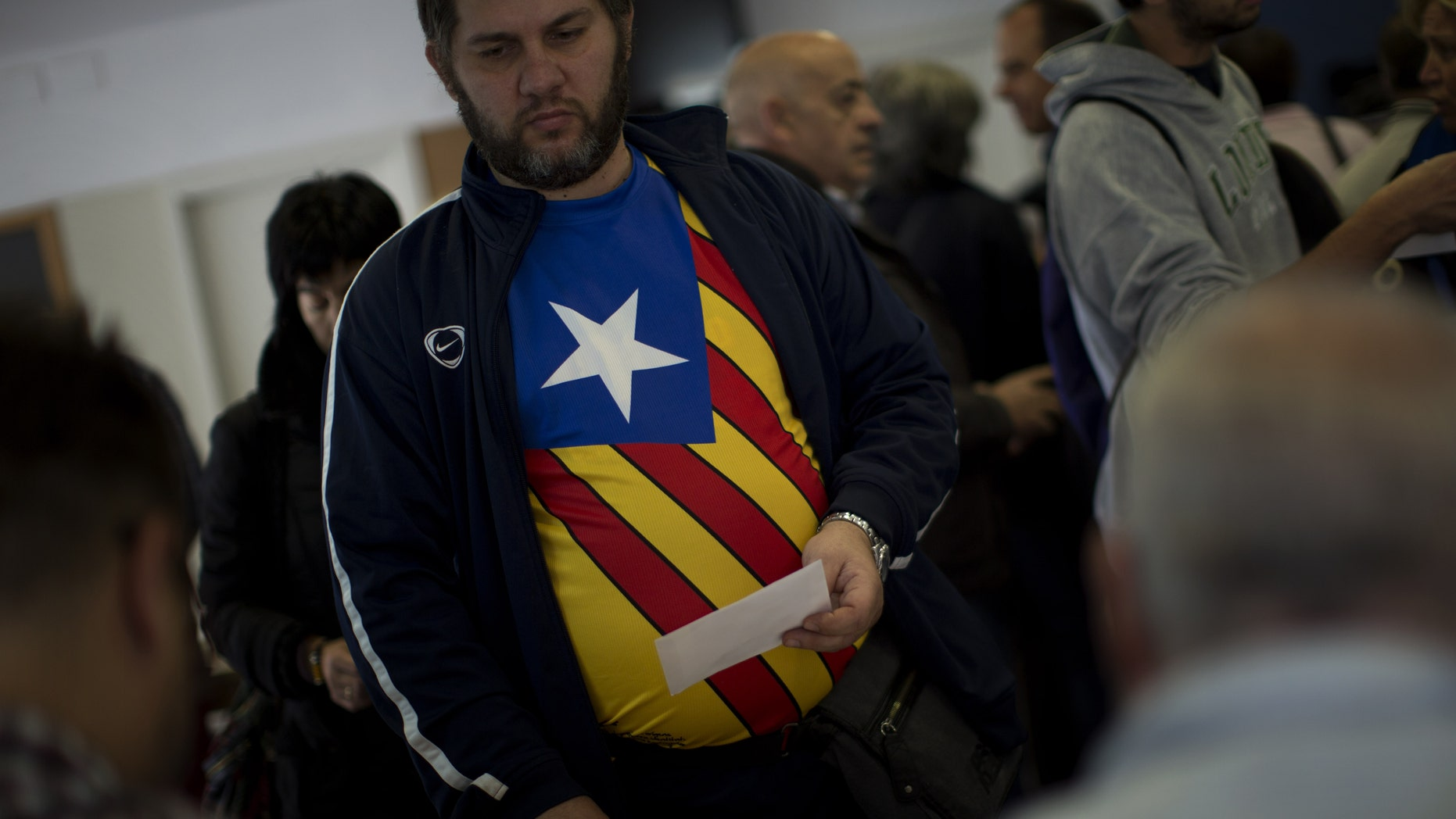 Carlas Albert, 45, waits to cast his vote for an informal independence poll in a polling station in Barcelona, Spain, on Sunday Nov.9, 2014. The pro-independence regional government of Catalonia stages a symbolic poll on secession in a show of determination and defiance after the Constitutional Court suspended its plans to hold an official independence referendum following a legal challenge by the Spanish government. (AP Photo/Emilio Morenatti)