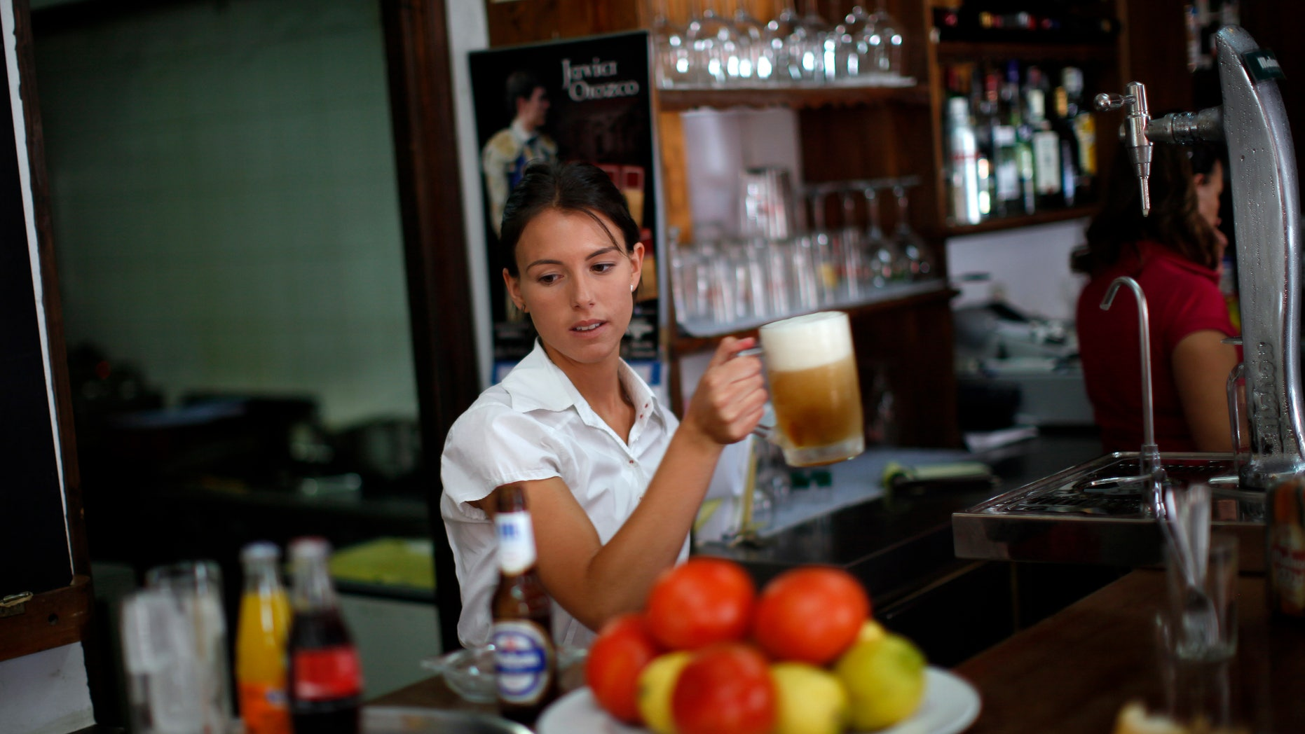 "July 24, 2014: Olalla Gomez, 22, a final-year student of English philology who is also on on the first day of her probation period before getting a contract as temporary waiter, holds a mug of beer in the ""Los Capeas"" restaurant in downtown Ronda, near Malaga, southern Spain."