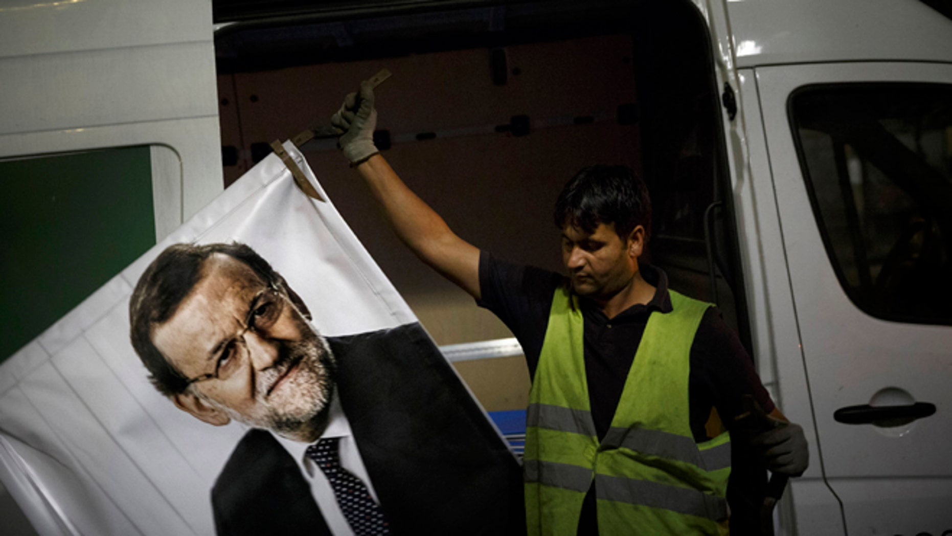 A worker removes a campaign poster for the national elections depicting Spain's Prime Minister and Popular Party candidate Mariano Rajoy, in Madrid, Spain, Monday, Dec. 21, 2015. A strong showing Sunday by a pair of upstart parties in Spain's general election upended the country's traditional two-party system, with the ruling Popular Party winning the most votes but falling far short of a parliamentary majority and at risk of being booted from power. (AP Photo/Daniel Ochoa de Olza)