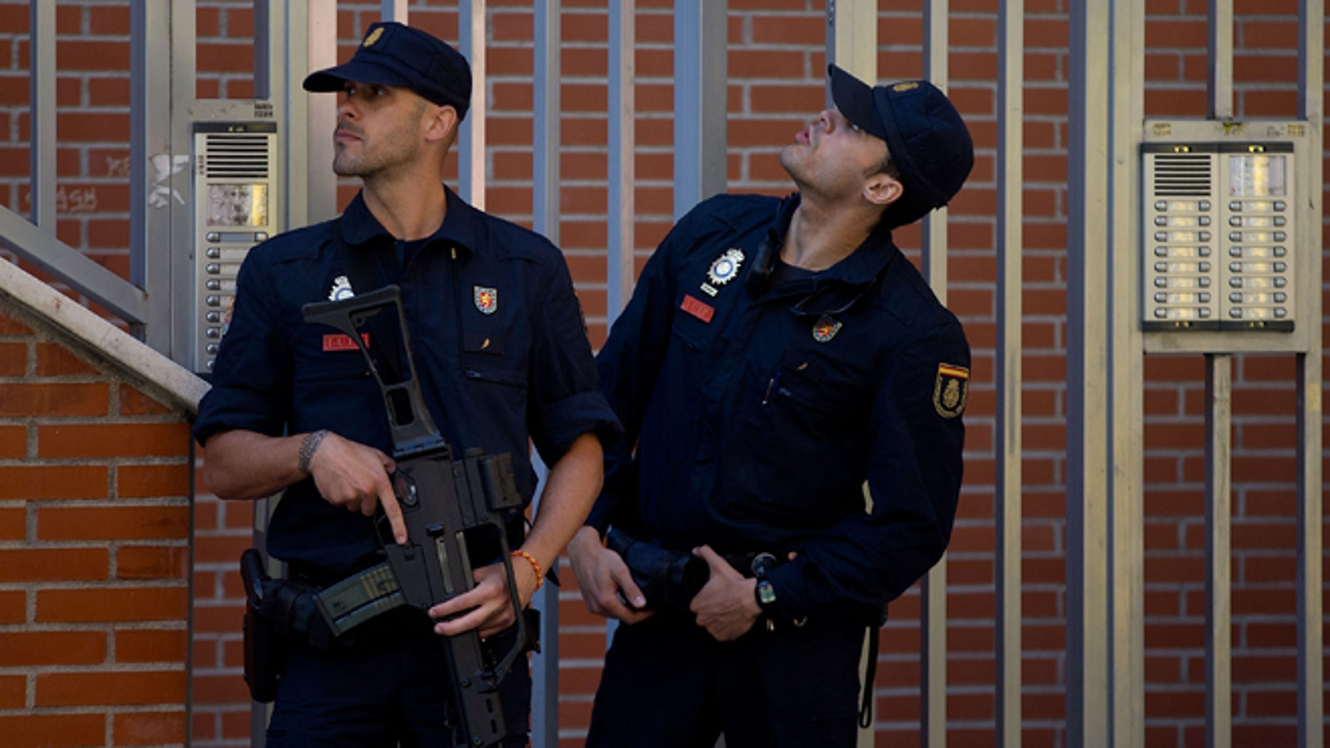 MADRID, SPAIN - JUNE 16:  Two Spanish policemen guard a residence at Rutilo street during an operation against an international Jihadist recruiting network on June 16, 2014 in Madrid, Spain. Spanish Police this morning made eight arrests in raids against an Islamist cell believed to be recruiting Jihadists to fight in Syria and Iraq for ISIL (Islamic State in Iraq and the Levant)Terrorist Group.  (Photo by Gonzalo Arroyo Moreno/Getty Images)