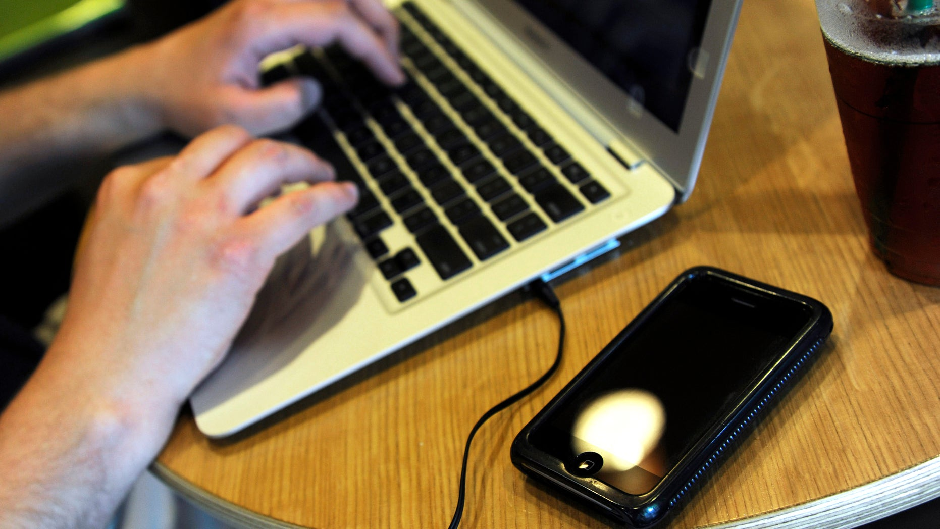 ** FOR USE MONDAY, DEC. 28 AND THEREAFTER ** FILE - In this May 13, 2009, file photo, Jonathan Hutcheson works on his laptop as his iPhone lays beside it at a coffee shop in Columbia, Mo. Wireless phone companies fear they're in danger of running out of room within the spectrum of wireless frequencies, so they want the government to give them bigger slices of airwaves _ even if other users have to give up rights to theirs. (AP Photo/L.G. Patterson, File)