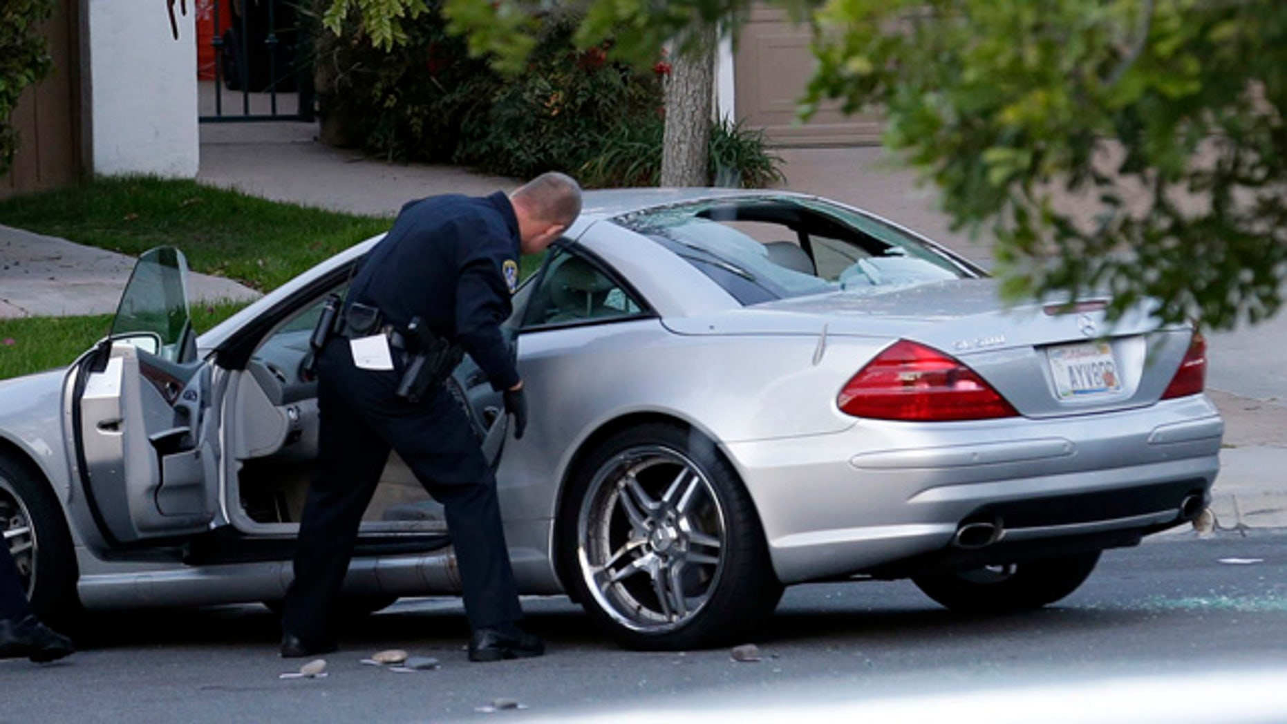 Feb. 10, 2015: Police examine the scene following a shooting in San Diego. CBS affiliate KFMB-TV says sports anchor Kyle Kraska was attacked Tuesday afternoon in the Scripps Ranch area of the city. (AP Photo/Gregory Bull)