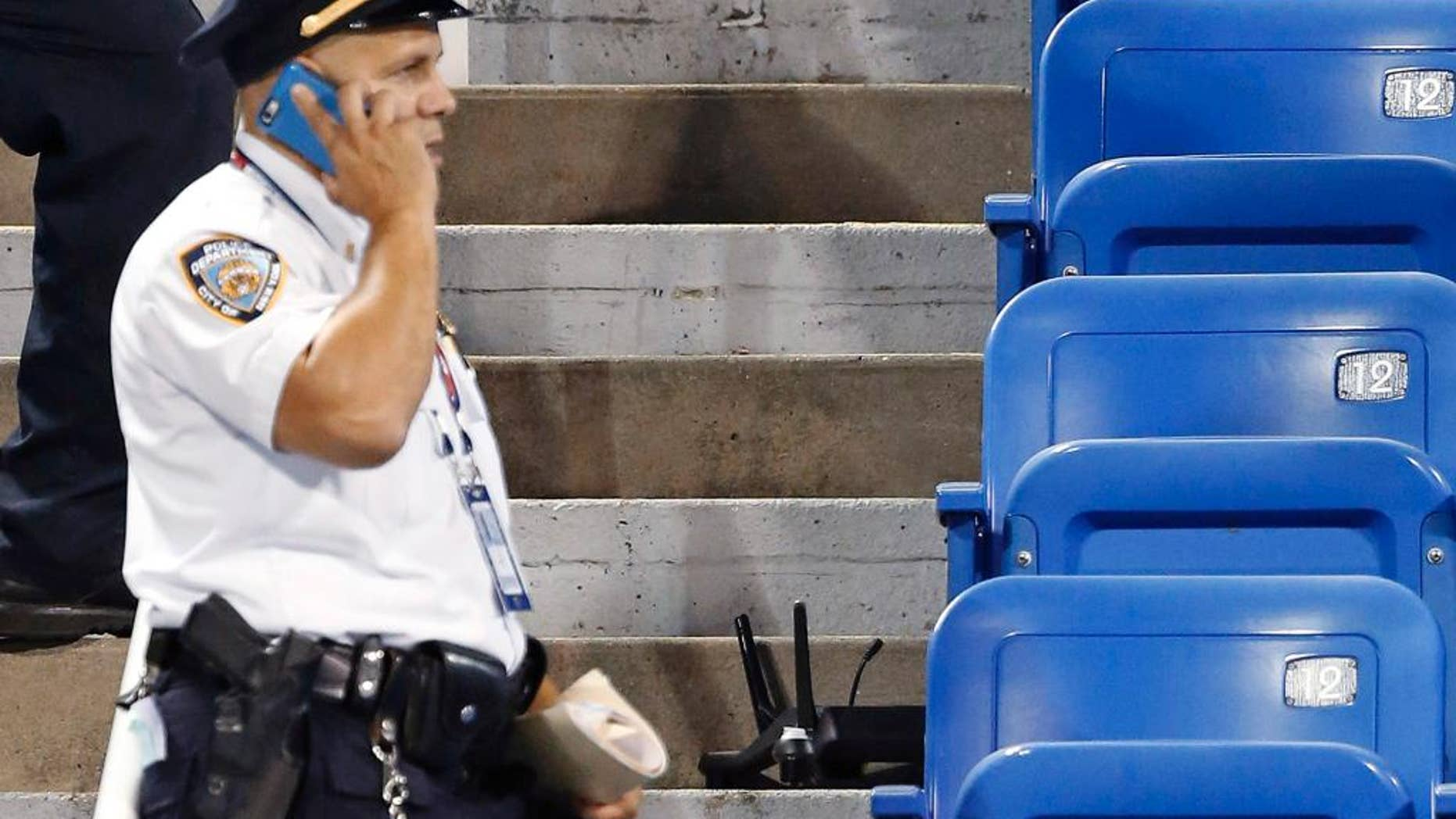 In this photo taken on Thursday, Sept. 3, 2015, police officers investigate the southwest corner of Louis Armstrong Stadium after a drone flew over the court, buzzing the players during a match between Flavia Pennetta, of Italy, and Monica Niculescu, of Romania, during the second round of the U.S. Open tennis tournament in New York. The drone crash-landed in the seats and can be seen to the right of the police officer on his phone. Whether they're crashing into the bleachers or simply hovering above stadiums to get a cool picture of the action down below, drones have become semi-regular guests at the ballparks these days. That has put the federal government, local police forces and security think tanks on alert, trying to catch up to the technology and figure out how to prevent the hard-to-stop devices from doing major damage. (AP Photo/Kathy Willens)