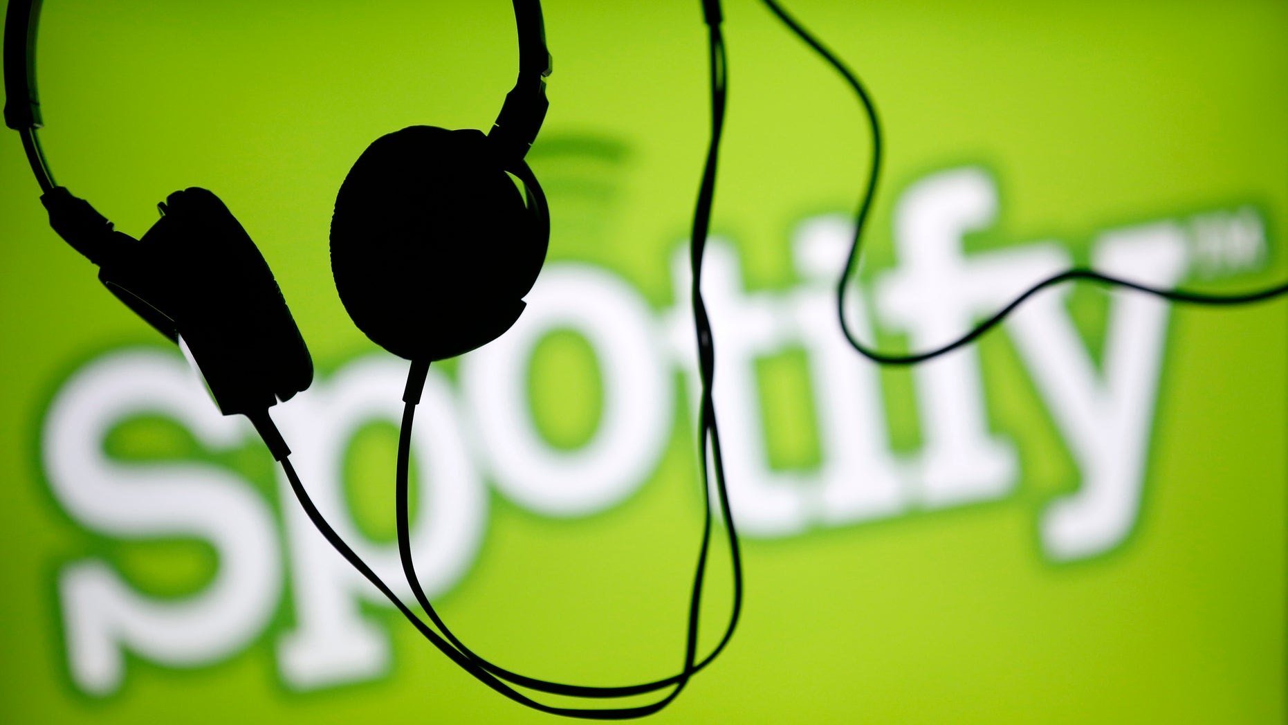 Headsets hang in front of a screen displaying a Spotify logo on it, in Zenica February 20, 2014. Online music streaming service Spotify is recruiting a U.S. financial reporting specialist, adding to speculation that the Swedish start-up is preparing for a share listing, which one banker said could value the firm at as much as $8 billion (4 billion pounds). REUTERS/Dado Ruvic (BOSNIA AND HERZEGOVINA - Tags: SCIENCE TECHNOLOGY BUSINESS SOCIETY) - RTX1975T