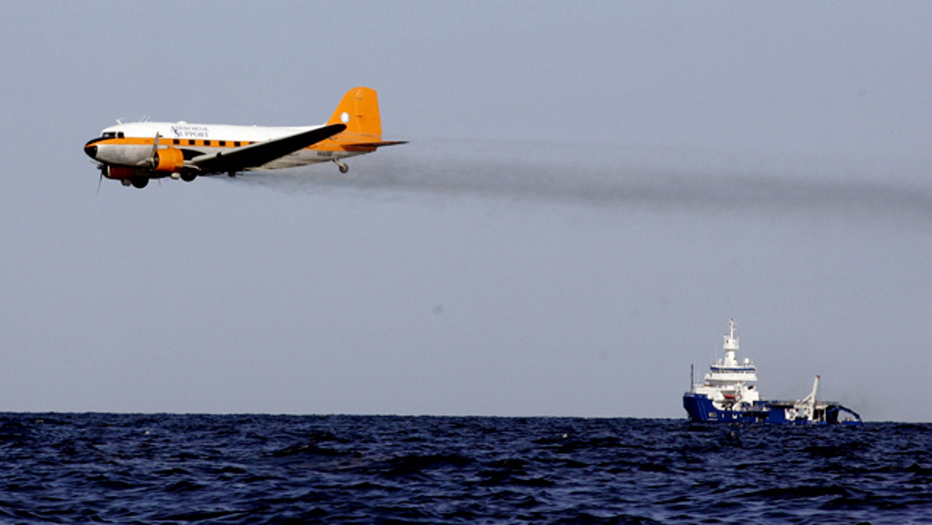 A dispersant plane passes over an oil skimmer as it cleans oil from a leaking pipeline that resulted from last week's explosion and collapse of the Deepwater Horizon oil rig in the Gulf of Mexico near the coast of Louisiana Tuesday, April 27, 2010.