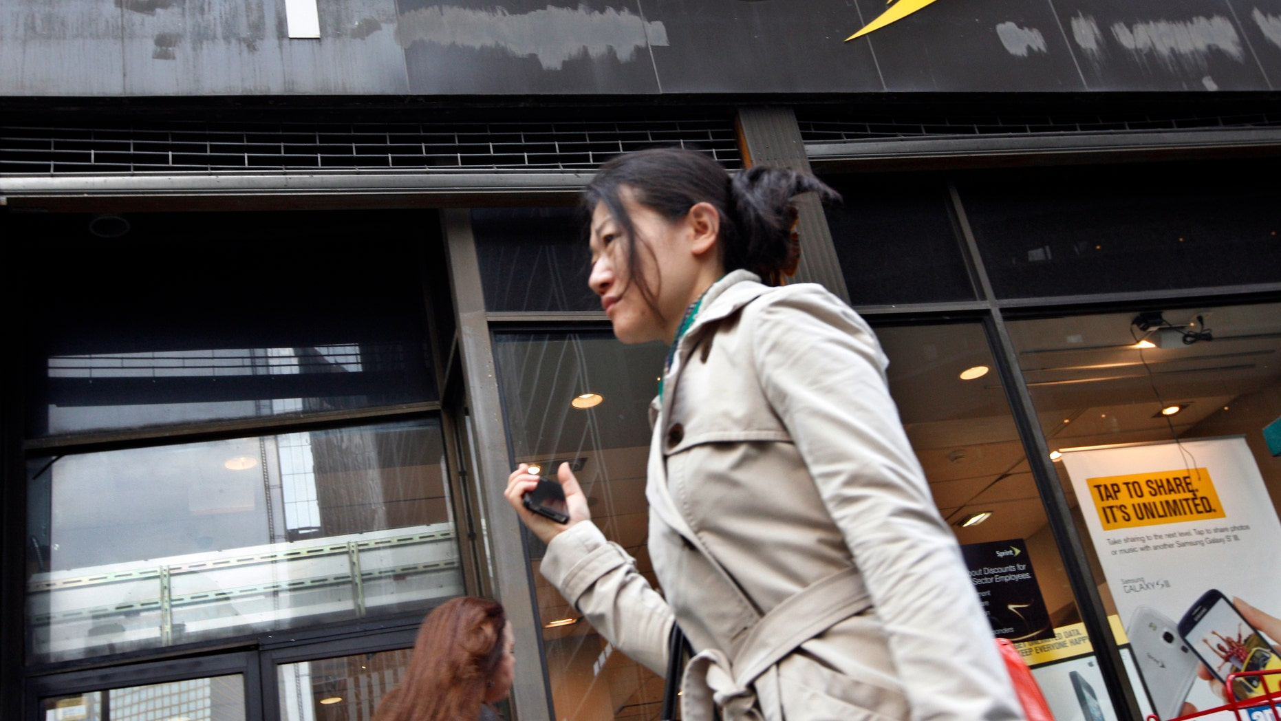 A woman walks past a Sprint store in New York's financial district, October 15, 2012.