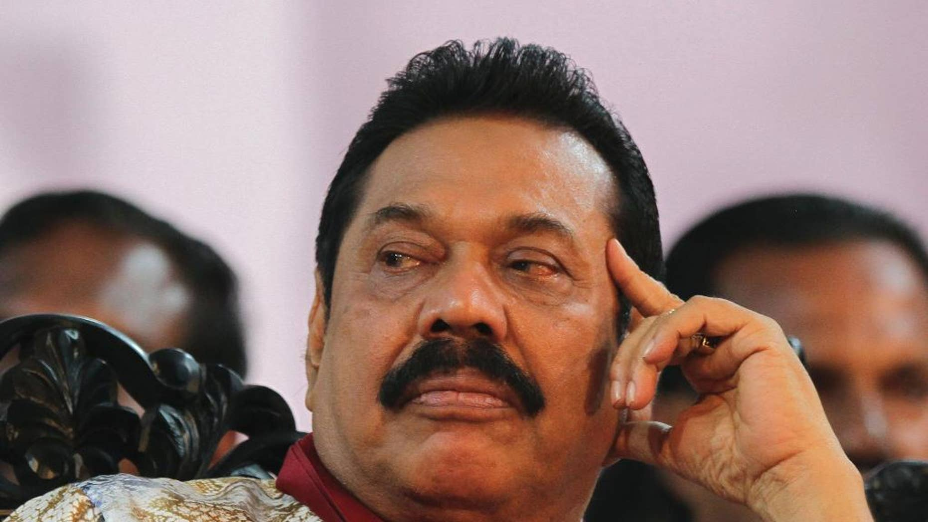 FILE - In this  Jan. 5, 2015 file photo, then-Sri Lankan President Mahinda Rajapaksa attends his final public rally for the presidential elections in Kesbewa, southeast of Colombo, Sri Lanka. Mangala Samaraweera, the spokesman for new President Maithripala Sirisena, said Sunday, Jan. 11, 2015, Sri Lanka's new government will investigate an alleged attempt by former President Rajapaksa to stage a coup to stay in power when results showed he was losing last week's election. (AP Photo/Sanka Gayashan, File)