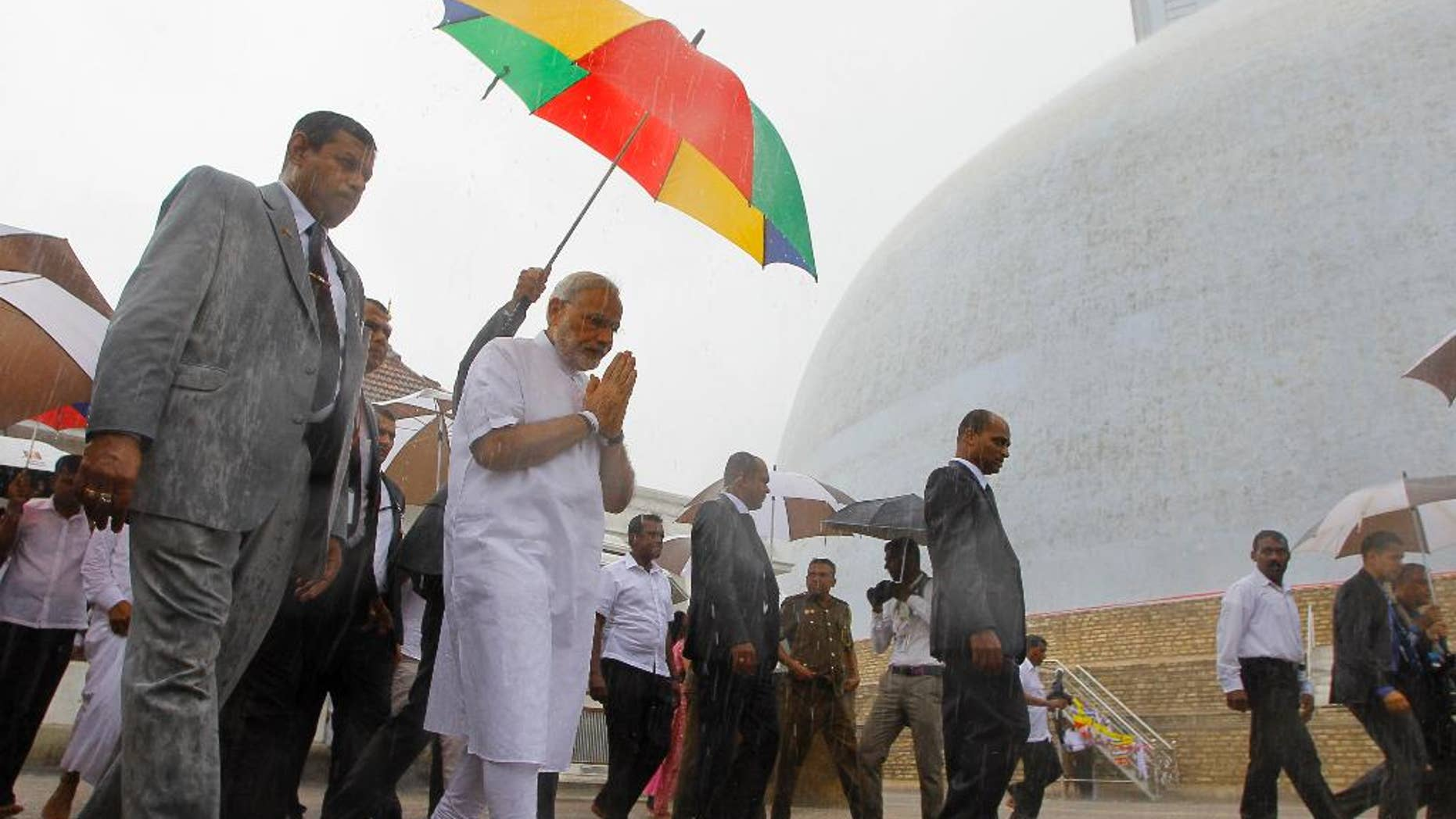 Indian Prime Minister Narendra Modi folds his hands in a sign of respect during his visit to Ruwanwelisaya, a sacred stupa in Anuradhapura, about 230 kilometers northeast of Colombo, Sri Lanka, Saturday, March 14, 2015. Modi said on Friday that India's neighbors should be the first beneficiaries of the nation's economic progress as he sought to woo smaller Indian Ocean states away from increasing Chinese influence. (AP Photo/Eranga Jayawardena)