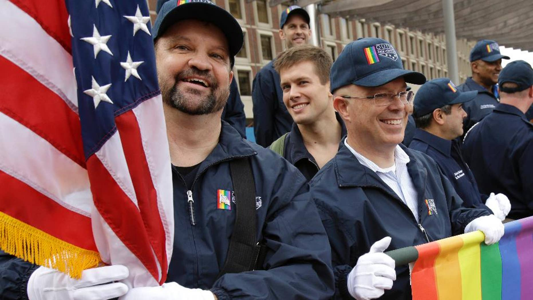 FILE - In this Nov. 11, 2014 file photo, retired U.S. Air Force Master Sgt. Eric Bullen, of Westborough, Mass., left, holds an American flag as U.S. Army veteran Ian Ryan, of Dennis, Mass., front right, rolls up an OutVets banner after marching with a group representing LGBT military veterans in a Veterans Day parade in Boston. The organizers of Boston's annual St. Patrick's Day parade voted to allow the group of gay  veterans along with a second gay group, Boston Pride, to march in the parade scheduled to step off at 1 p.m., on Sunday, March 15, 2015. (AP Photo/Steven Senne, File)