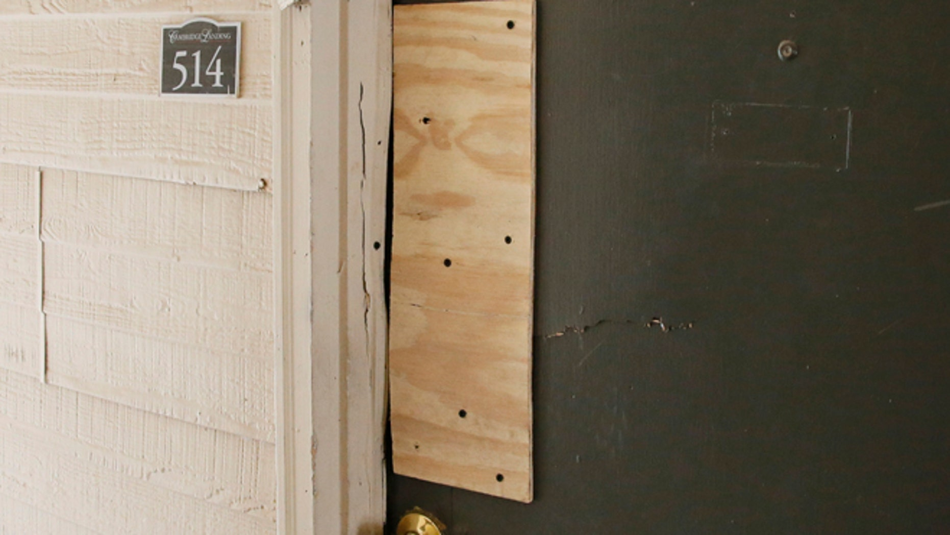 The boarded-up door of an apartment where Oklahoma City police have arrested a mother on suspicion of stabbing a man and her two children, the youngest of which was pronounced dead when police arrived on scene, is pictured in Oklahoma City, Monday, July 11, 2016. (AP Photo/Sue Ogrocki)
