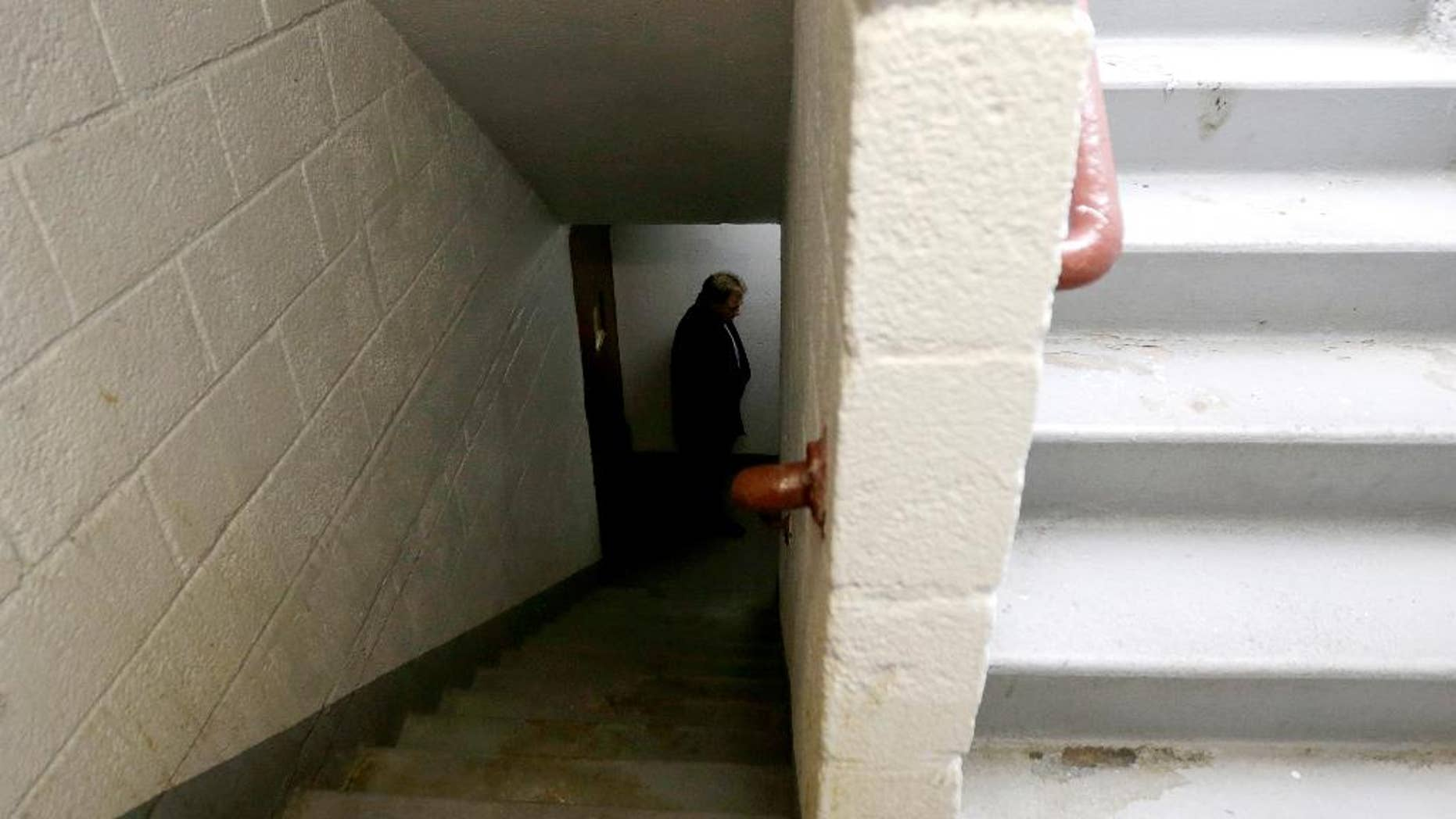 FILE - In this Nov. 21, 2014, file photo, a man who identified himself as a detective with the district attorney's office inspects a stairwell at the Louis Pink Houses public housing complex in Brooklyn borough of New York. Officer Peter Liang who fired into the darkened stairwell, accidentally killing Akai Gurley who had been waiting for an elevator, has been indicted in his death, a lawyer said Tuesday, Feb. 10, 2015. Liang will appear in court Wednesday according to an attorney representing Gurley's family, but the charges against Liang weren't immediately clear. (AP Photo/Julio Cortez, File)