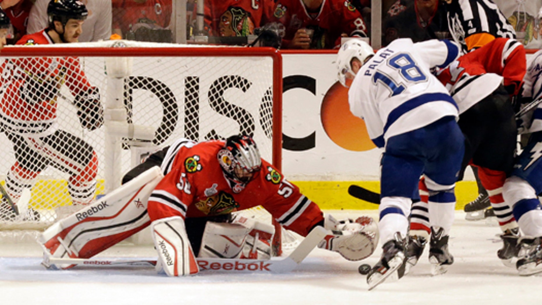 June 8, 2015: The Tampa Bay Lightning's Ondrej Palat (18) scores past Chicago Blackhawks goalie Corey Crawford (50) during the third period in Game 3 of the NHL hockey Stanley Cup Final in Chicago. (AP Photo/Charles Rex Arbogast)