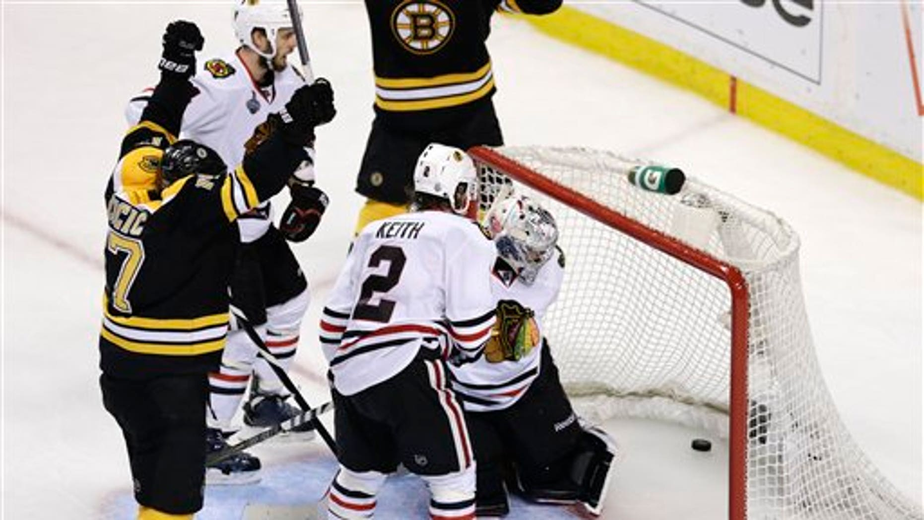 June 24, 2013: Boston Bruins left wing Milan Lucic, left, reacts after scoring past Chicago Blackhawks defenseman Duncan Keith (2) and goalie Corey Crawford, hidden during the third period in Game 6 of the NHL hockey Stanley Cup Finals.