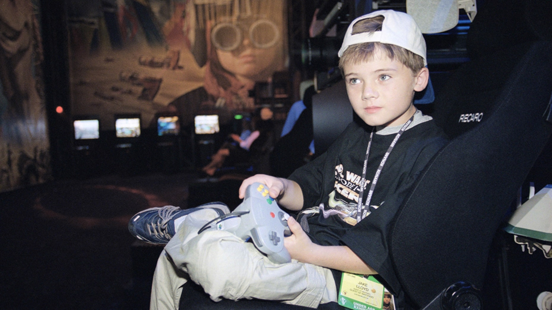 """FILE- In this May 13, 1999, file photo, actor Jake Lloyd; who portrays young Anakin Skywalker in the film """"Star Wars Episode I: The Phantom Menace;"""" plays a game during the Electronic Entertainment Expo in Los Angeles."""