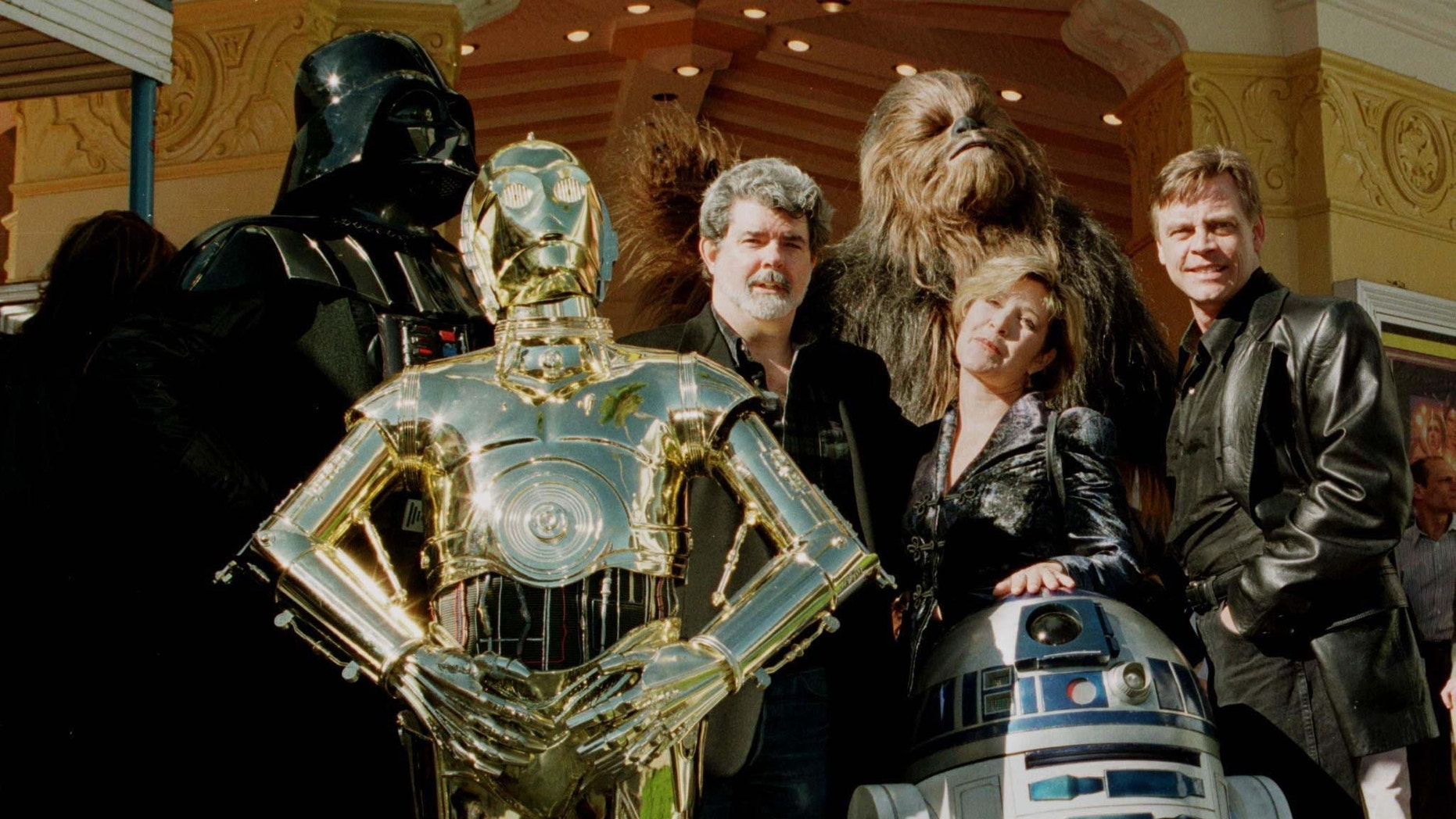 """Director and writer of """"Star Wars,"""" George Lucas (C) poses with cast members Carrie Fisher and Mark Hamill along with characters """"Darth Vader"""" (L) """"3CPO"""" (in gold) """"R2D2"""" (short robot) and """"Chewbacca"""" (background) during the premiere of """"Star Wars Special Editon"""" January 18, 1997 in Los Angeles."""
