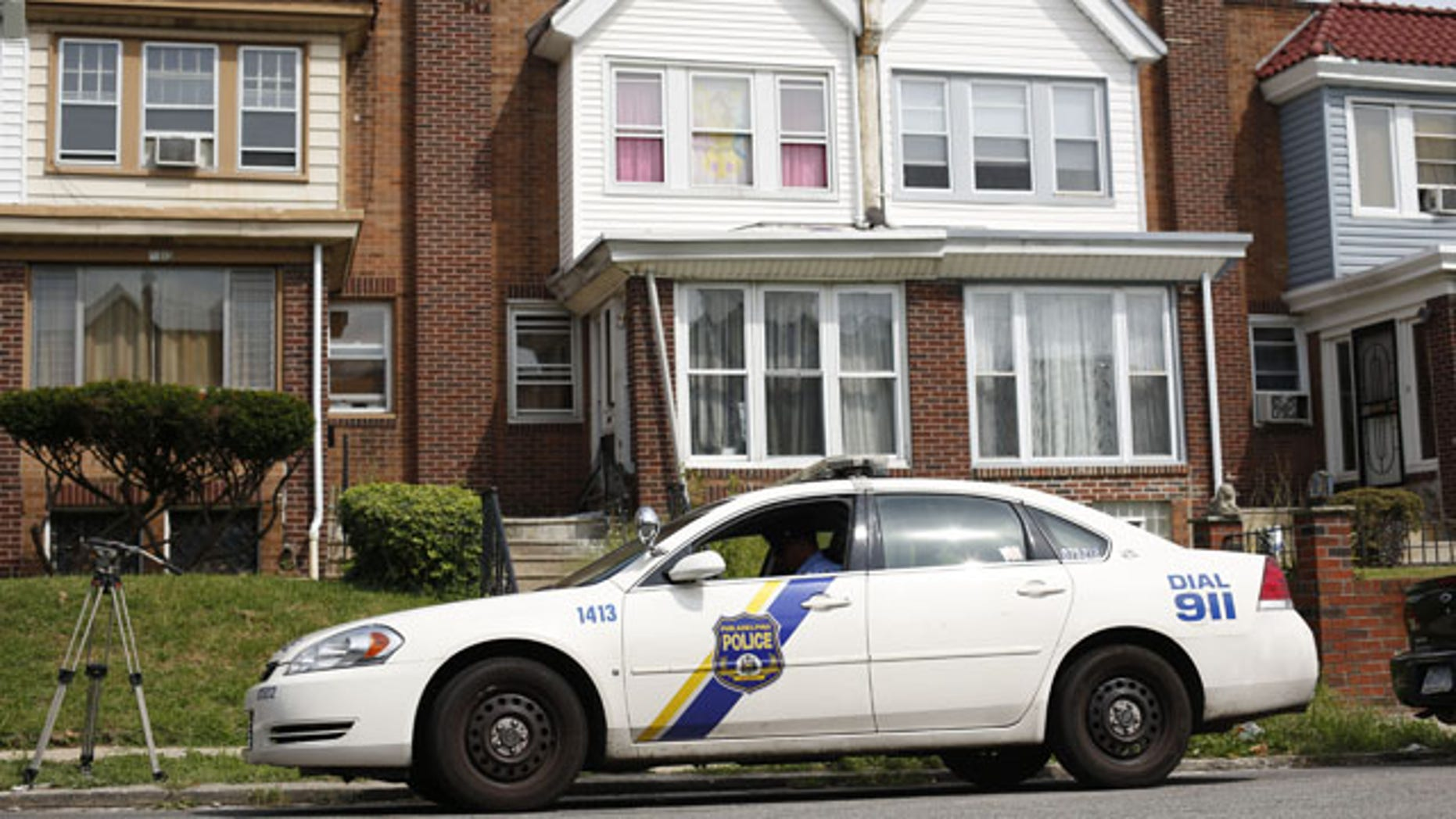 September 9, 2013: A police officer sits outside the home of a severely disabled 3-year-old girl who was pronounced dead at a nearby hospital in Philadelphia. Nathalyz Rivera, a twin, weighed just 11 pounds when she died and police in Philadelphia called her death a homicide. (AP Photo/Matt Rourke)