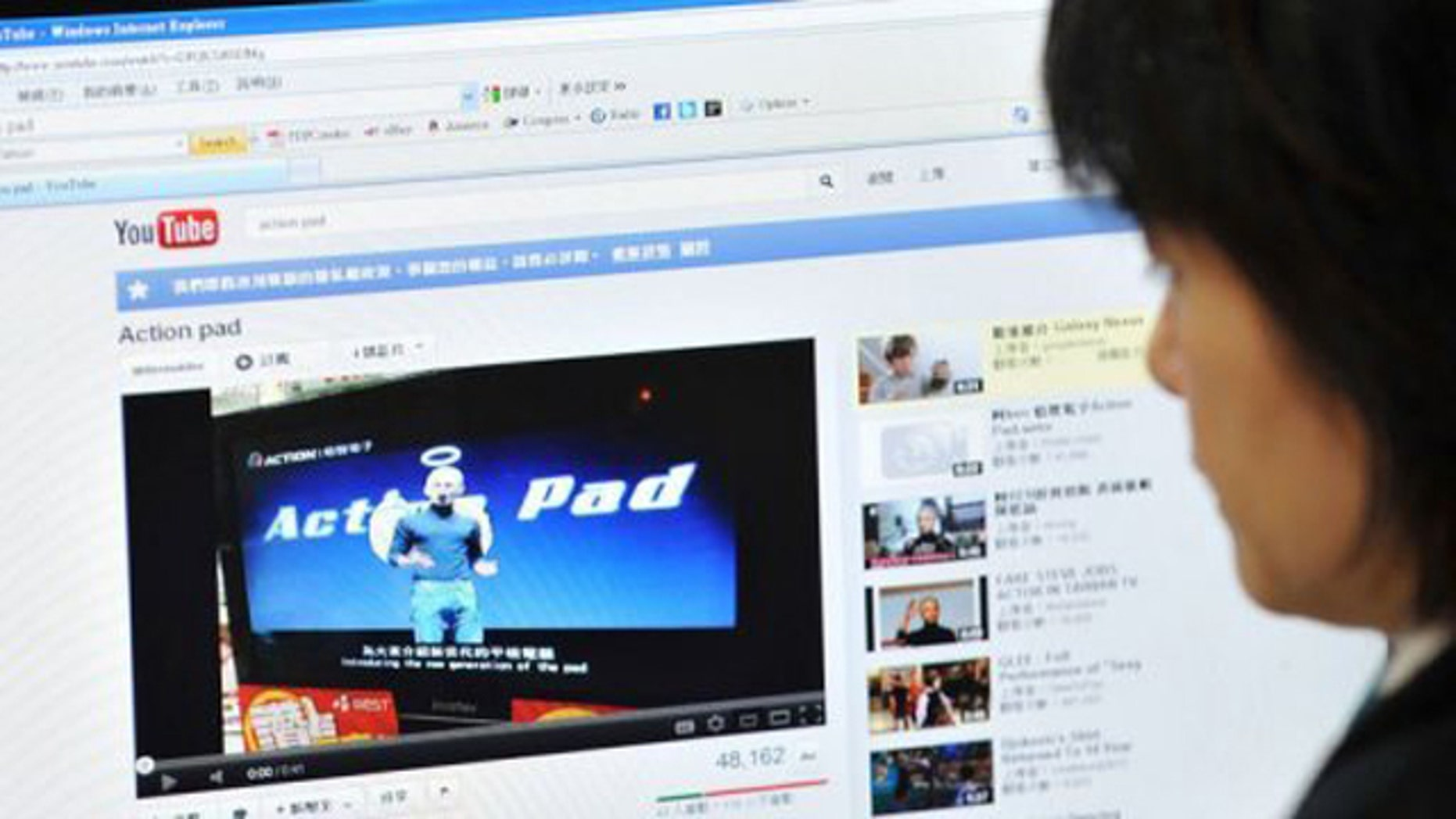 A woman looks at an Internet website in Taipei showing Taiwanese comedian A-Ken dressed up as Apple's late founder.