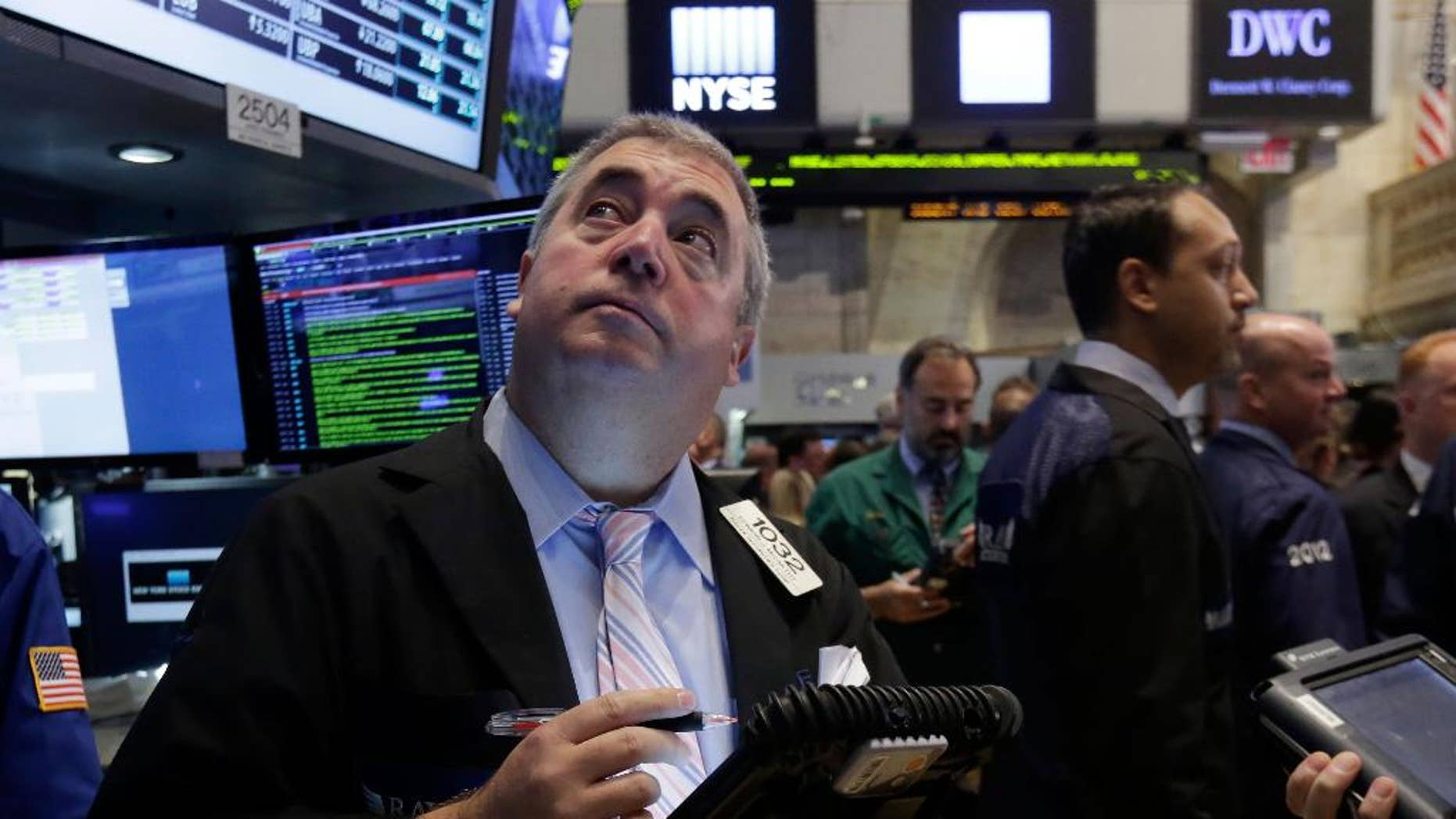 FILE - In this Thursday, Aug. 21, 2014, file photo, trader Edward McCarthy, left, works on the floor of the New York Stock Exchange. As stocks continue to rise, investors are wondering if it's time to sell. (AP Photo/Richard Drew, File)