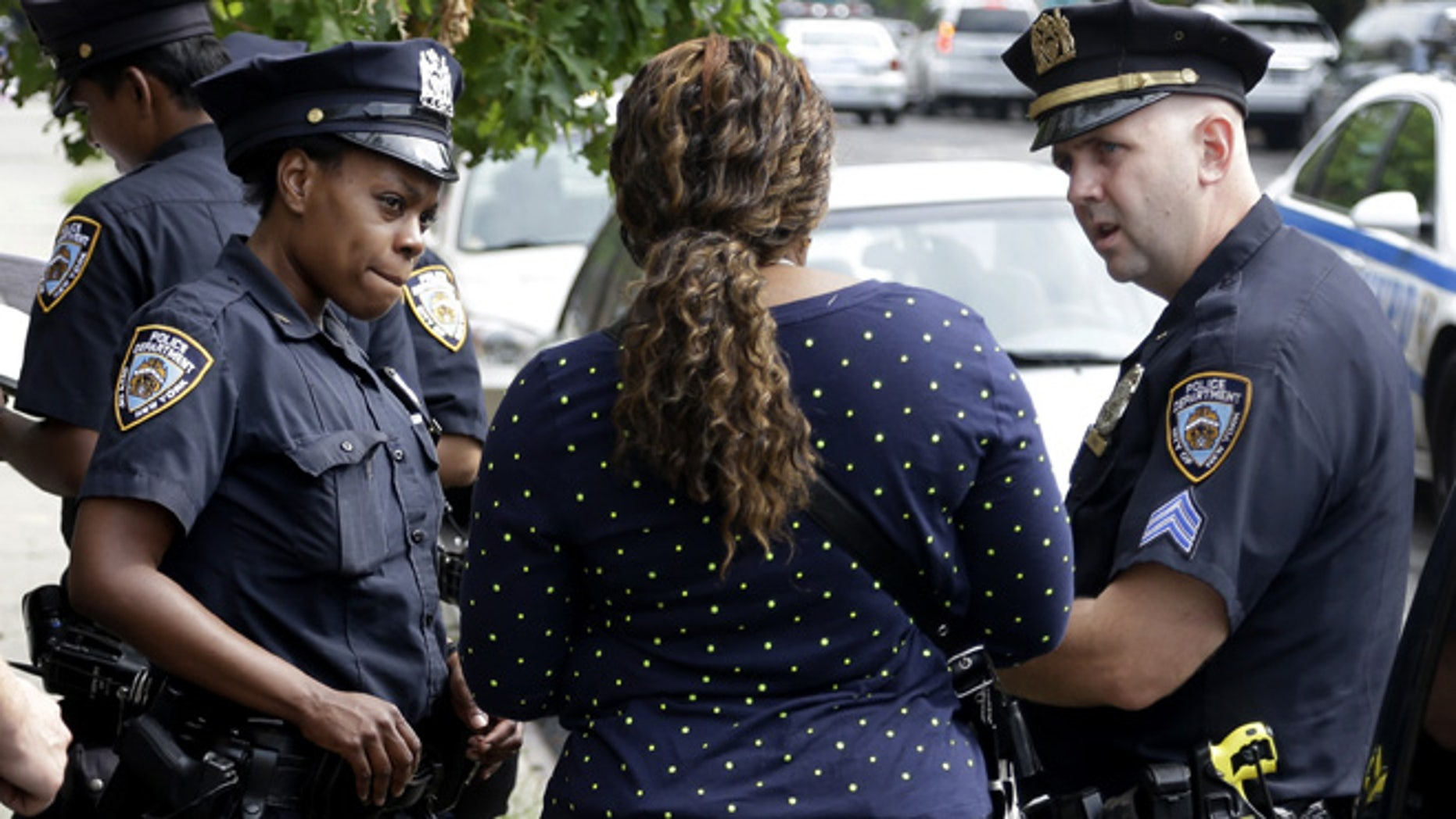 "Police officers talk with a woman who had her phone stolen in the Brownsville section of Brooklyn, New York, Tuesday, Aug. 13, 2013. A federal judge's stinging rebuke of the police department's stop-and-frisk policy as discriminatory could usher in a return to the days of high violent crime rates and end New York's tenure as ""America's safest big city,"" Mayor Michael Bloomberg warned. (AP Photo/Seth Wenig)"